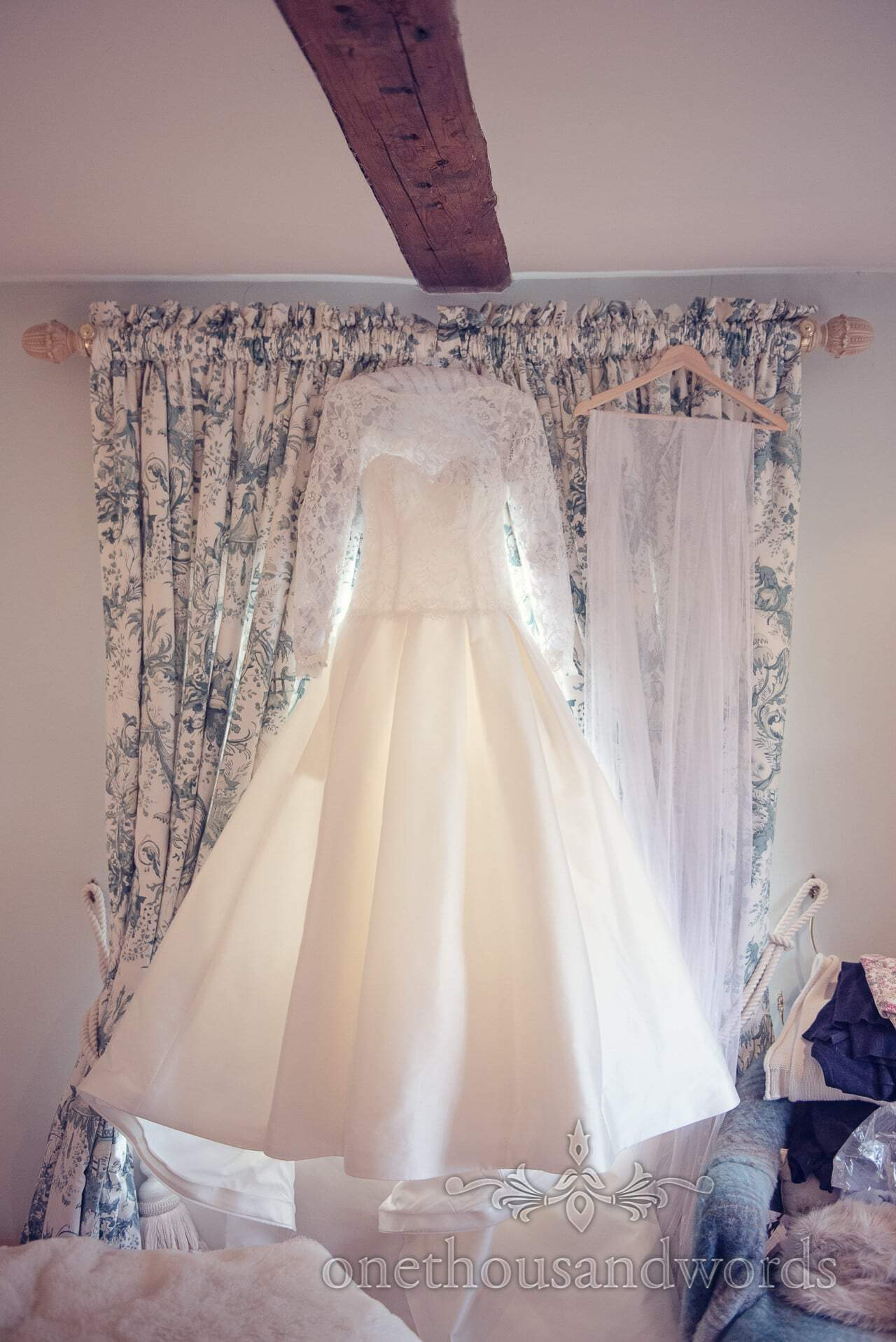 Custom wedding dress with pockets hanging in window with veil