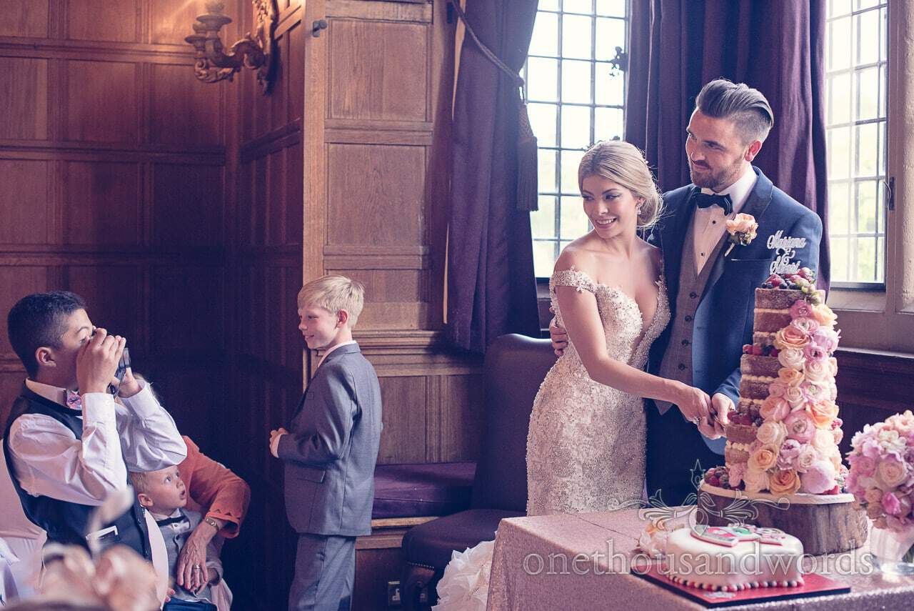 Cutting the cake at Rhinefield House Hotel wedding