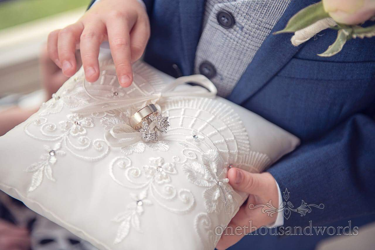 Diamond and white gold wedding rings on pillow held by page boy