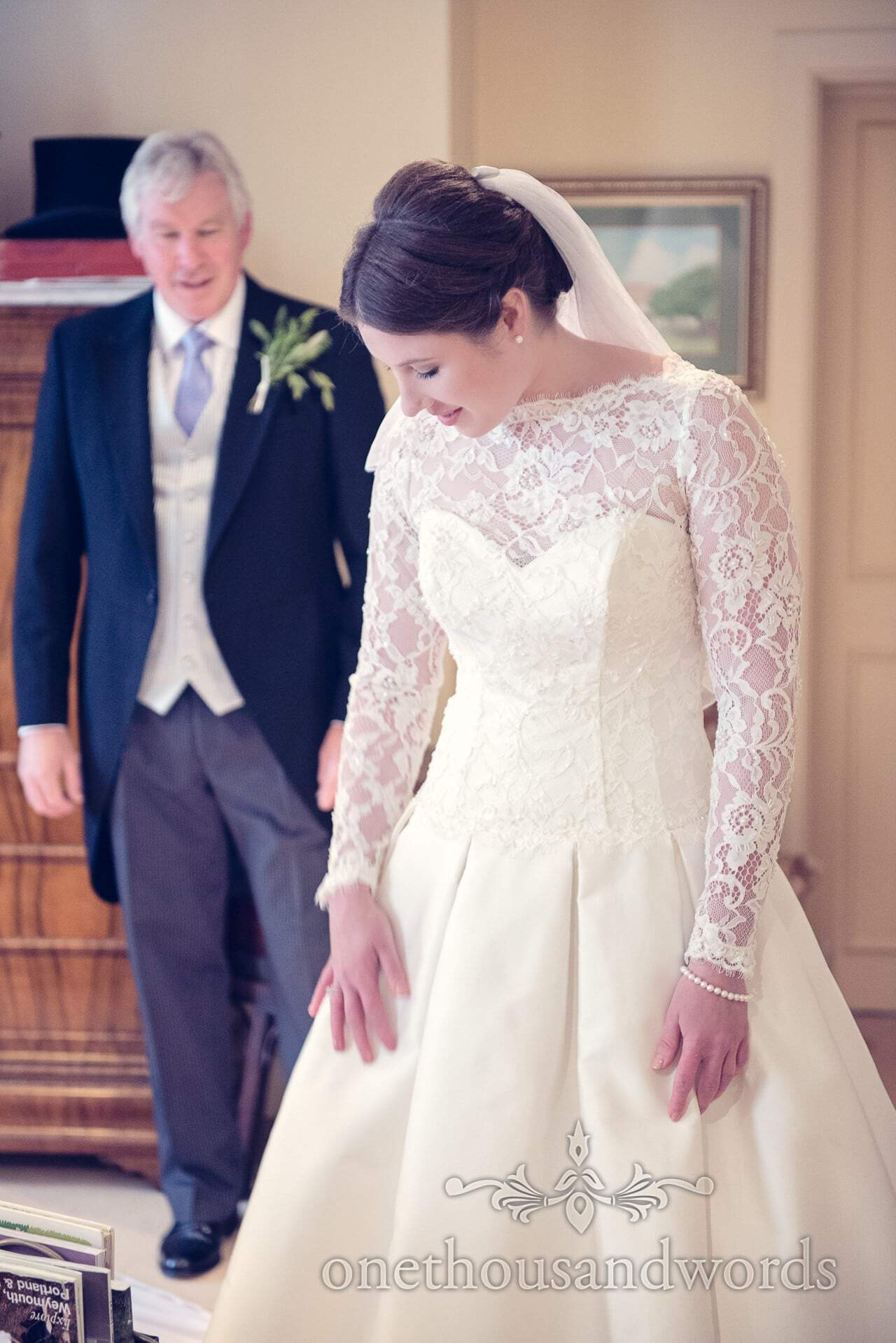 Father of bride looks at bride in white wedding dress on wedding morning