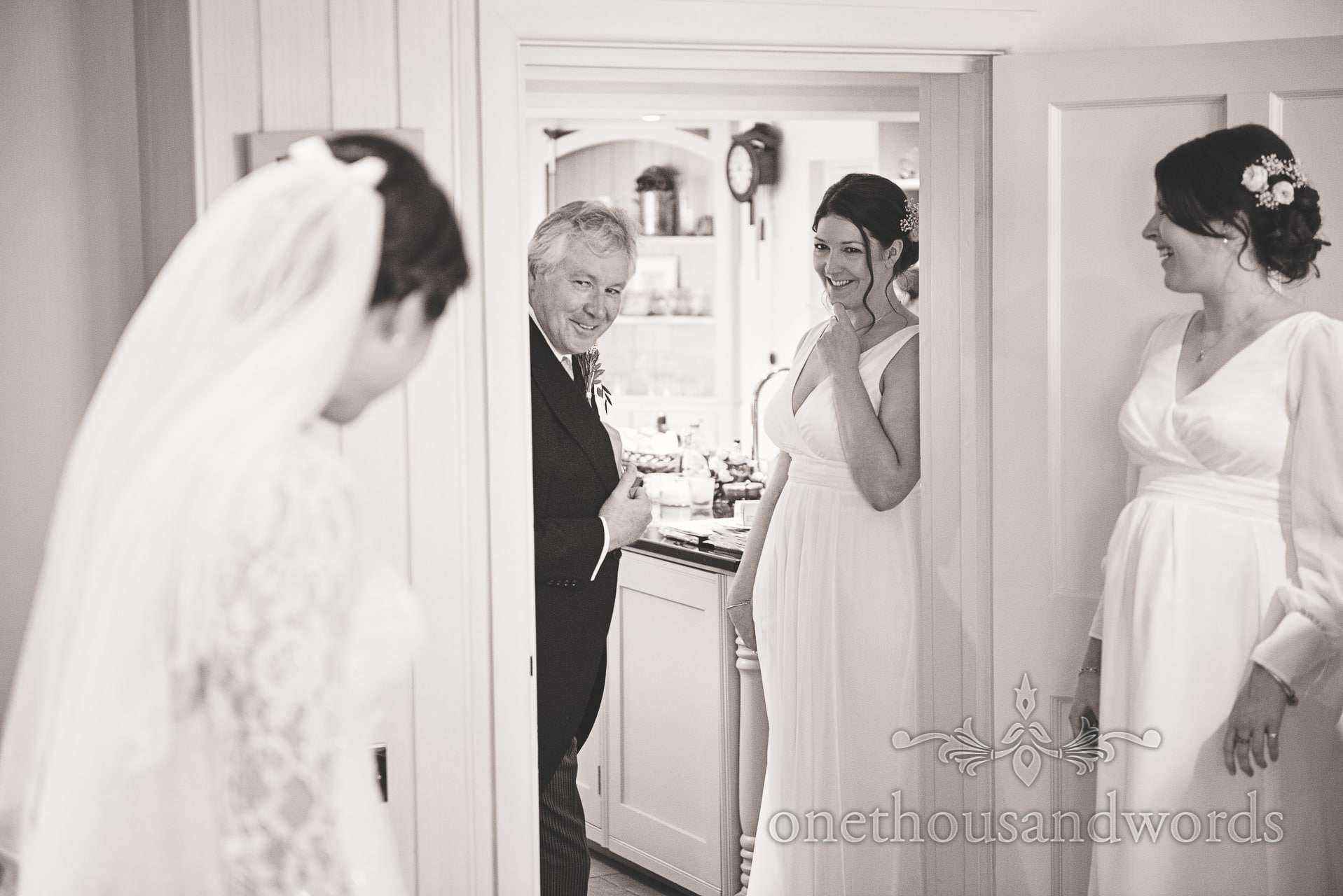 Father of bride looks at daughter in wedding dress for first time