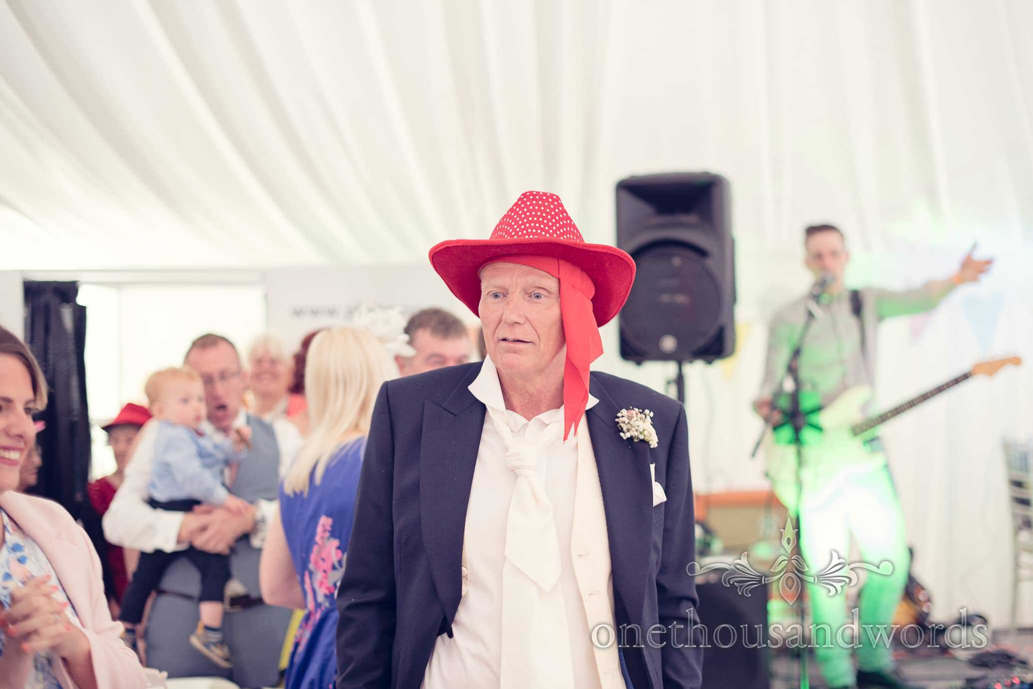Father of groom dances in red cowboy hat fancy dress at Deans Court wedding