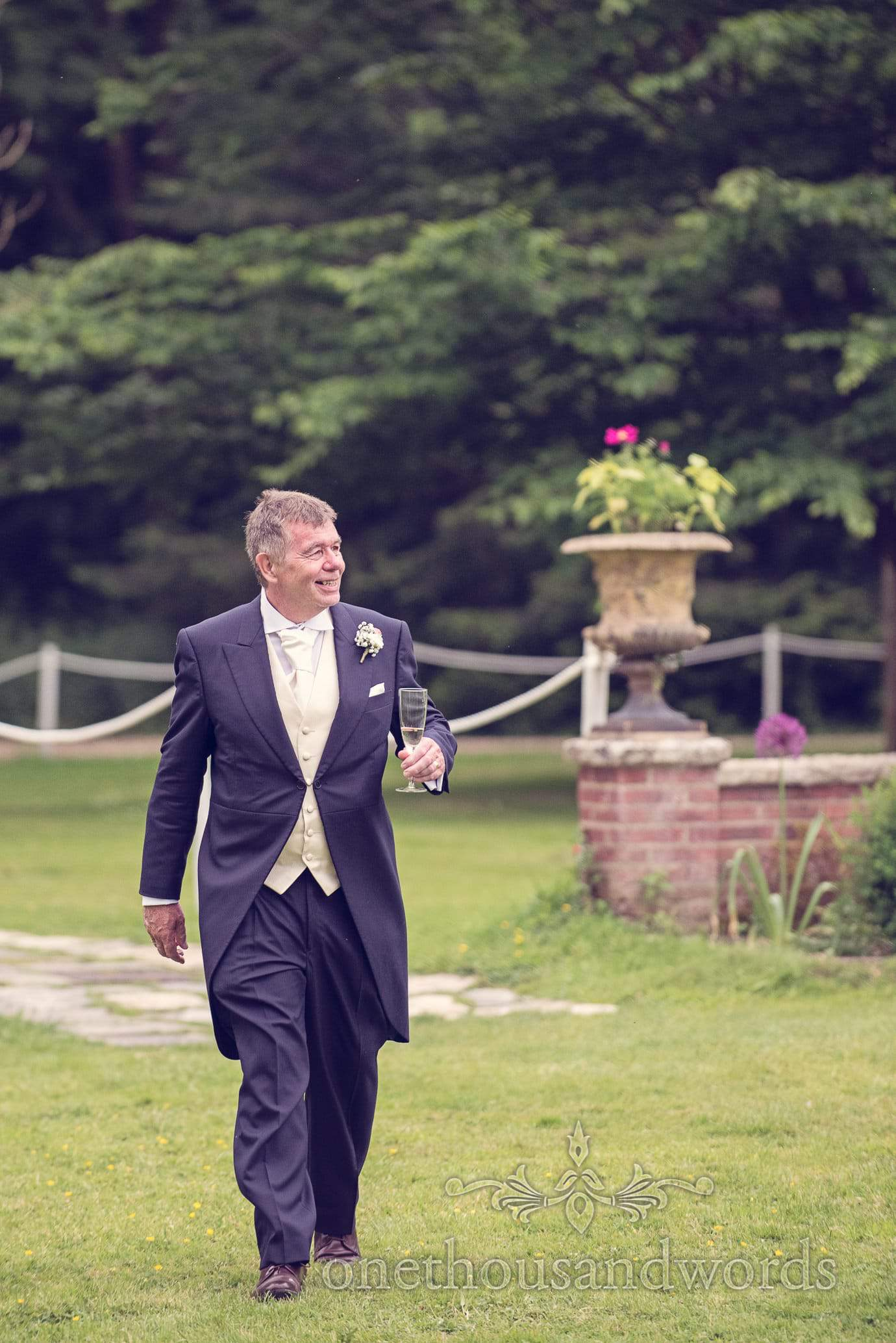 Father of the bride at drinks reception in the gardens at Deans Court Wedding
