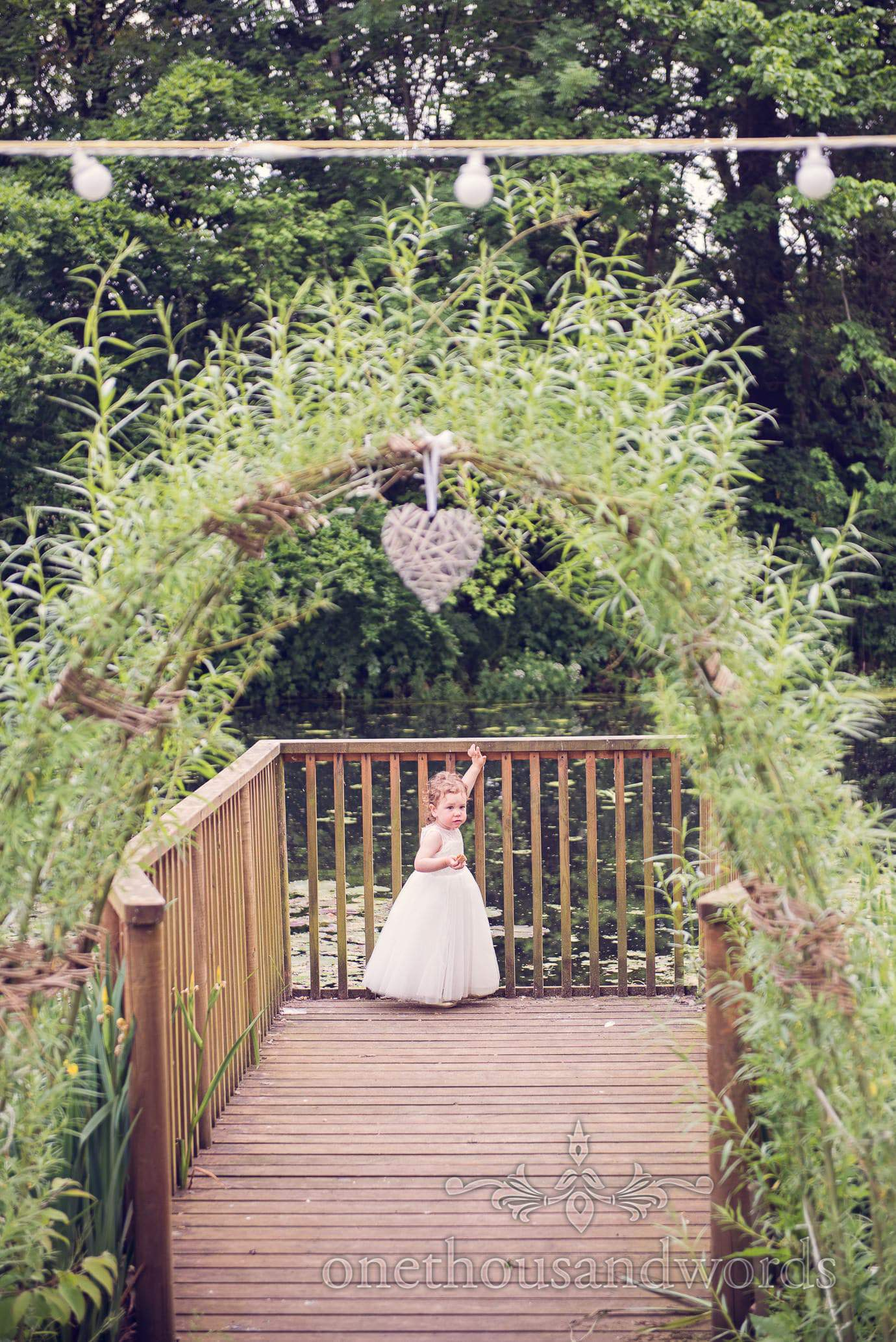 Flower Girl under floral archway with wicker love heart at Deans Court Wedding