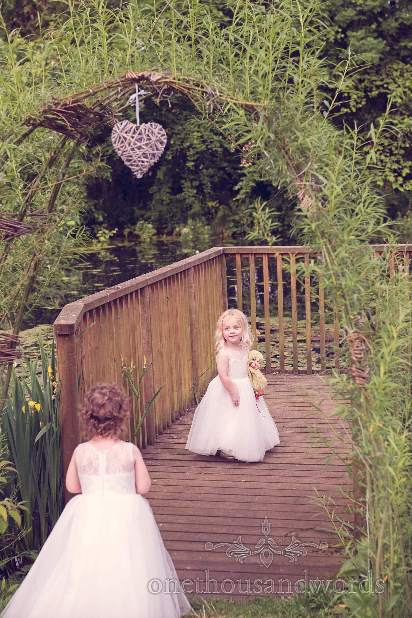 Flower girls on wooden pontoon next to lake at Deans Court Wedding