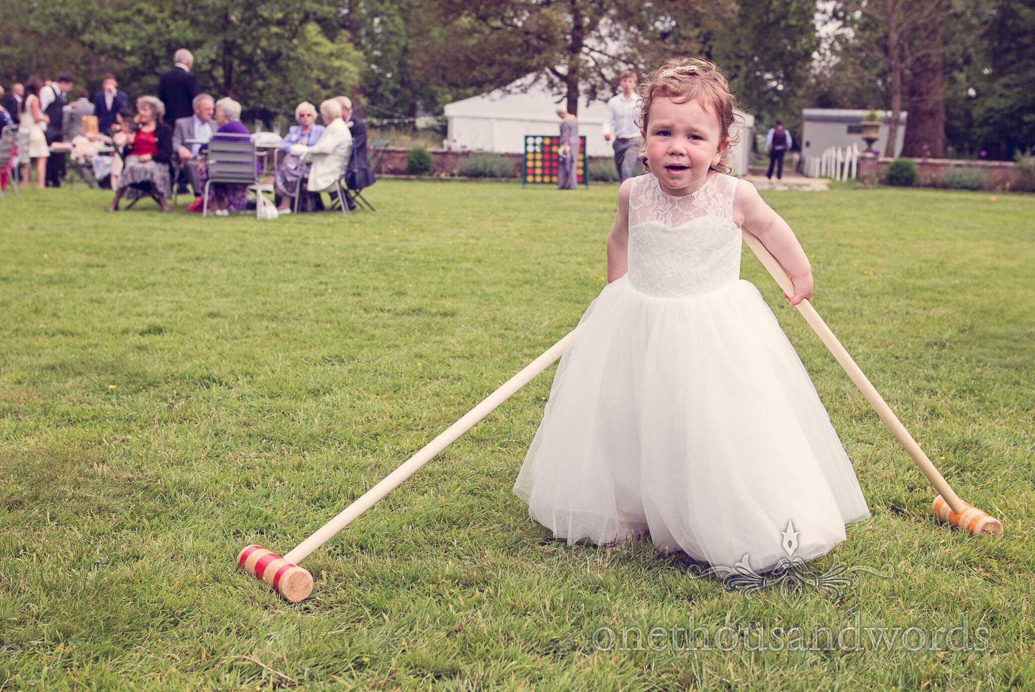Flower girls with croquet mallets and garden games at Deans Court wedding
