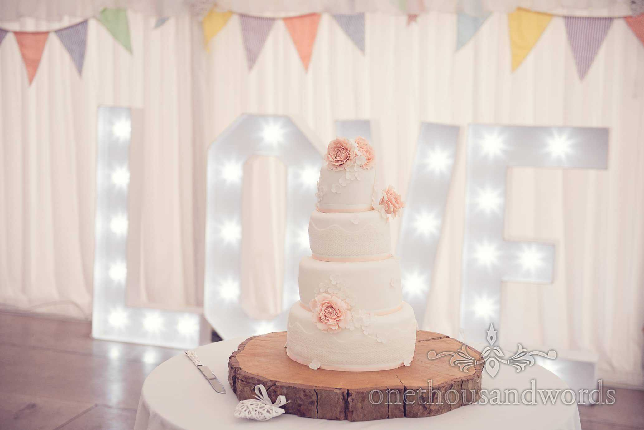 four tier wedding cake with love sign and bunting at Deans Court wedding