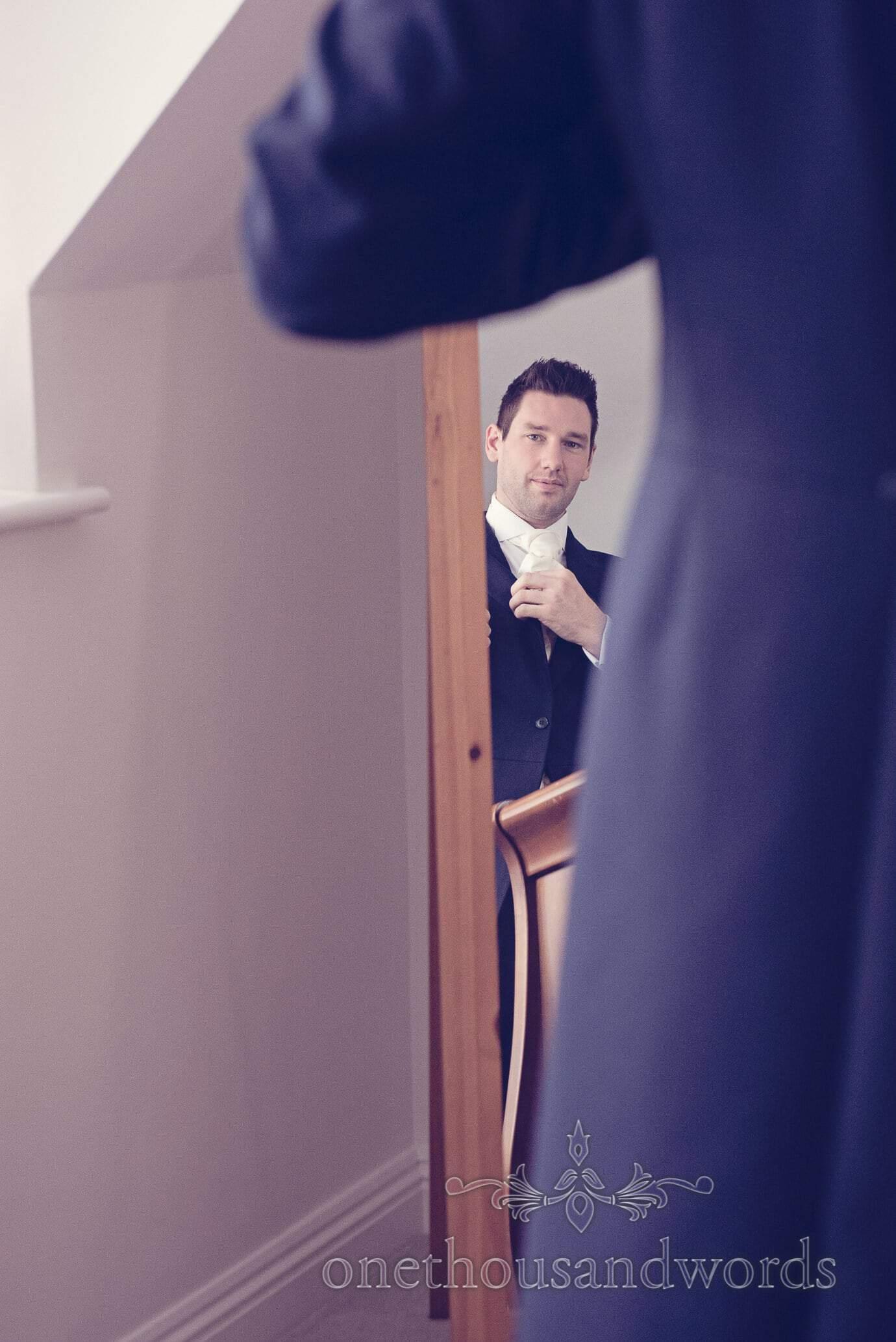 Groom adjusts cravatte in mirror on wedding morning