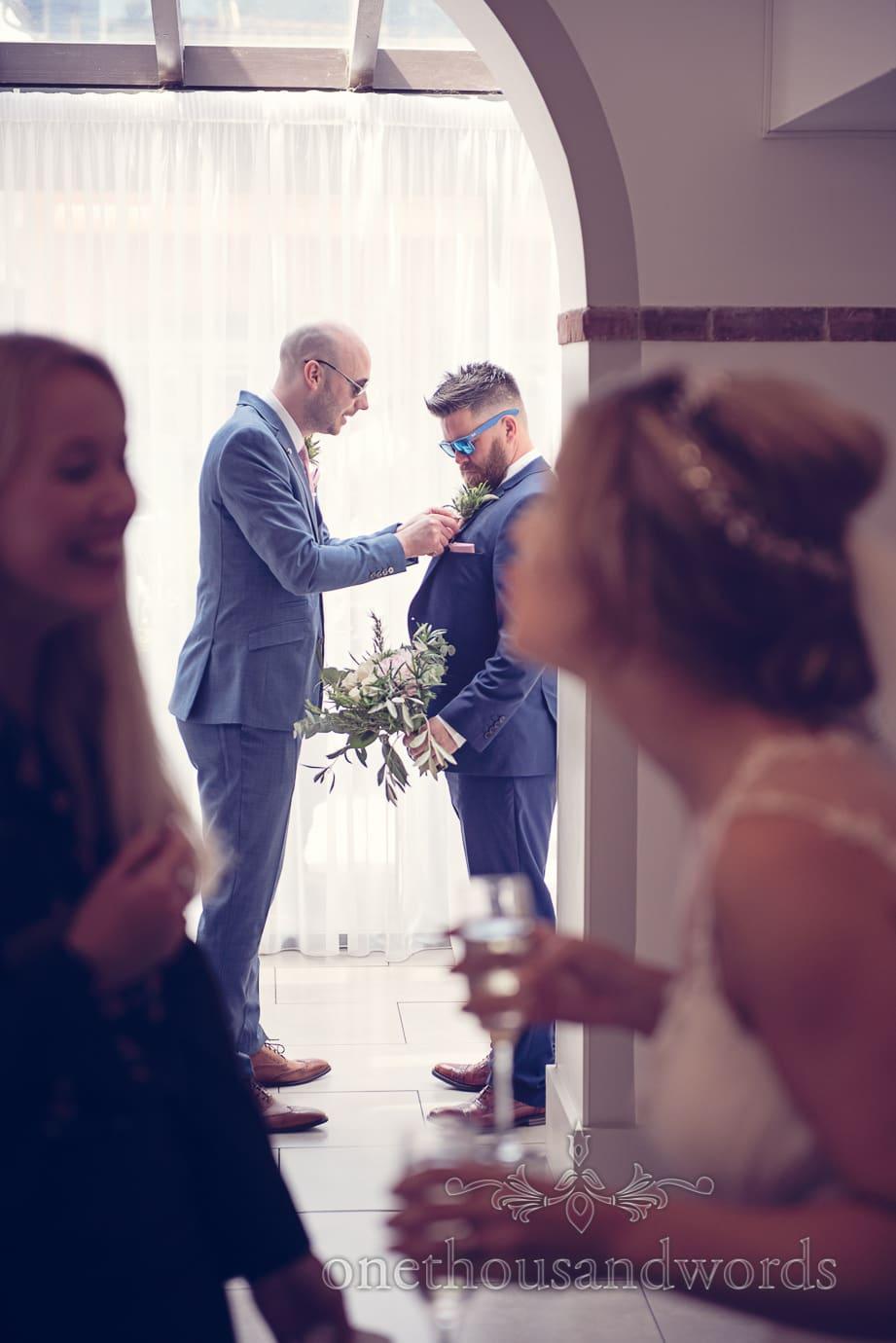 Groom adjusts groomsman's buttonhole at Italian Villa Wedding Photographs