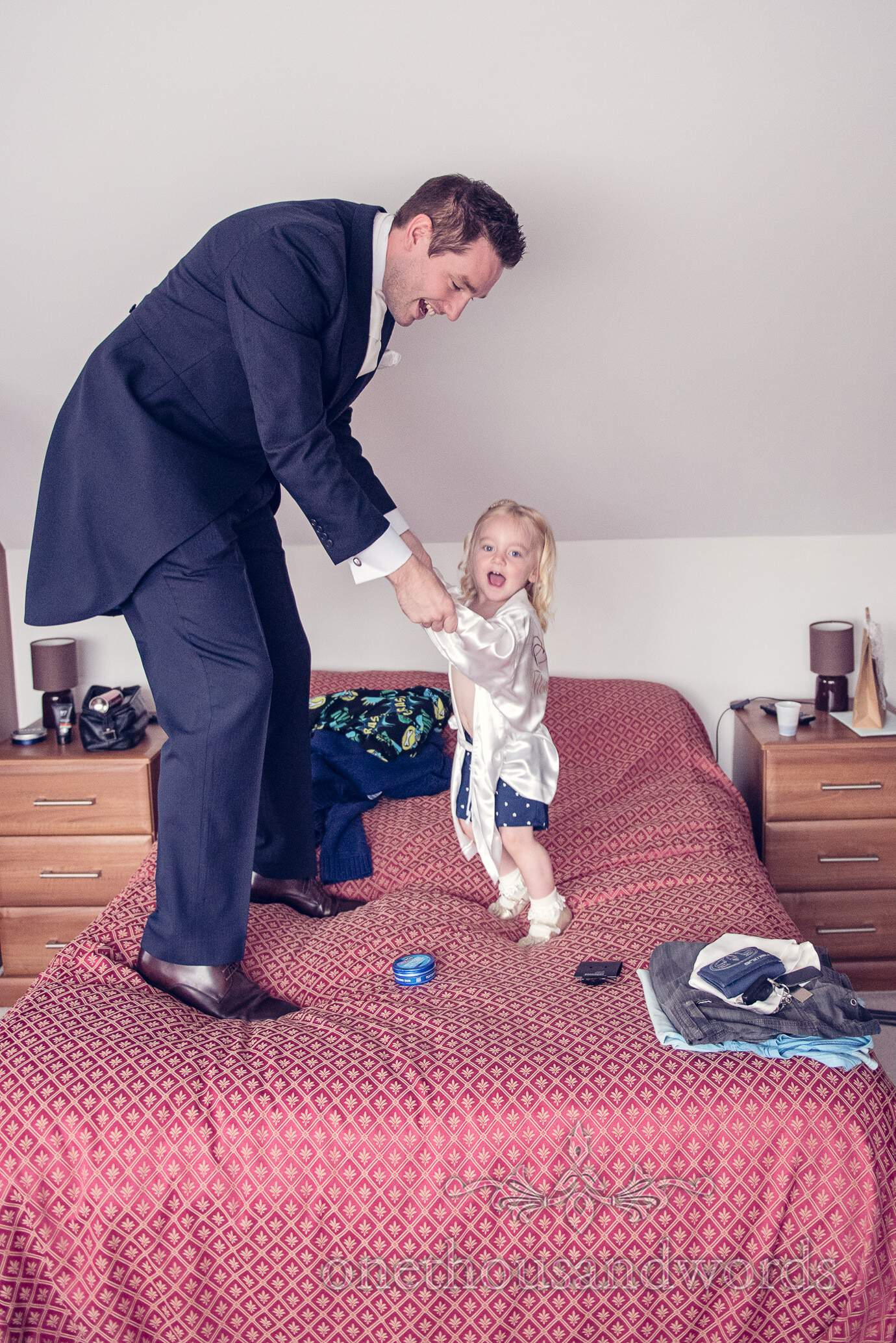 Groom and flower girl bounce on bed on wedding morning