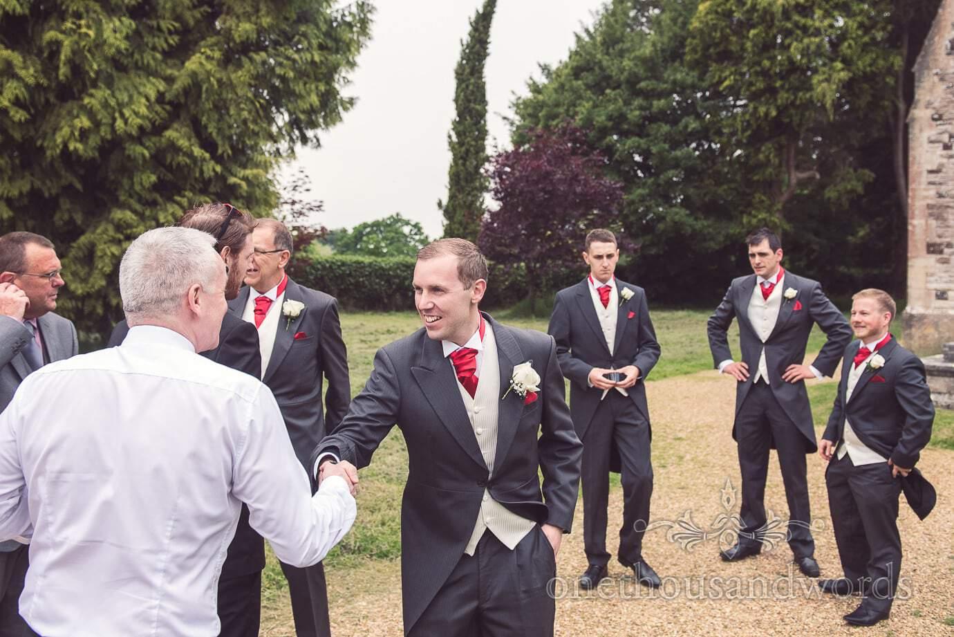 Groom and groomsmen greet wedding guests outside Dorset Church