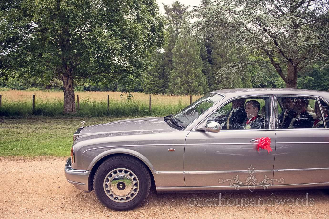Groom and groomsmen travel to church wedding in grey Rolls Royce