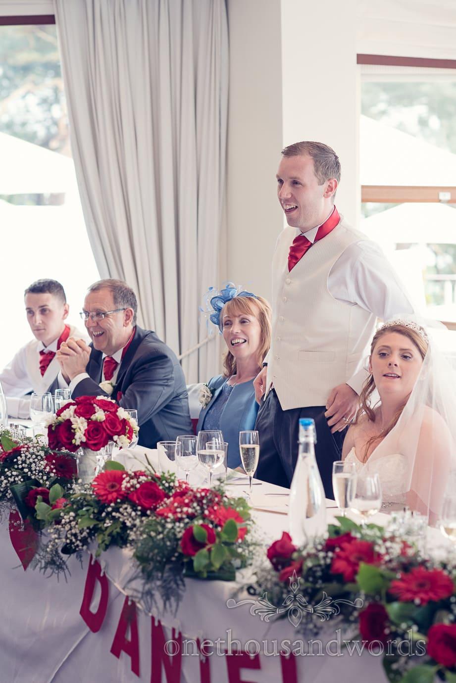 Groom in red tie makes grooms speech at Harbour Heights wedding photos