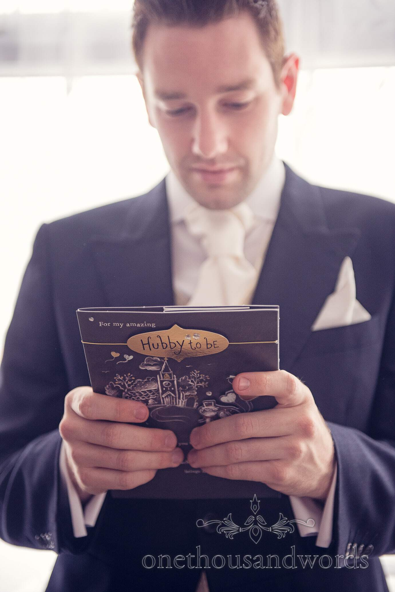 Groom reads card from his wife to be on wedding morning