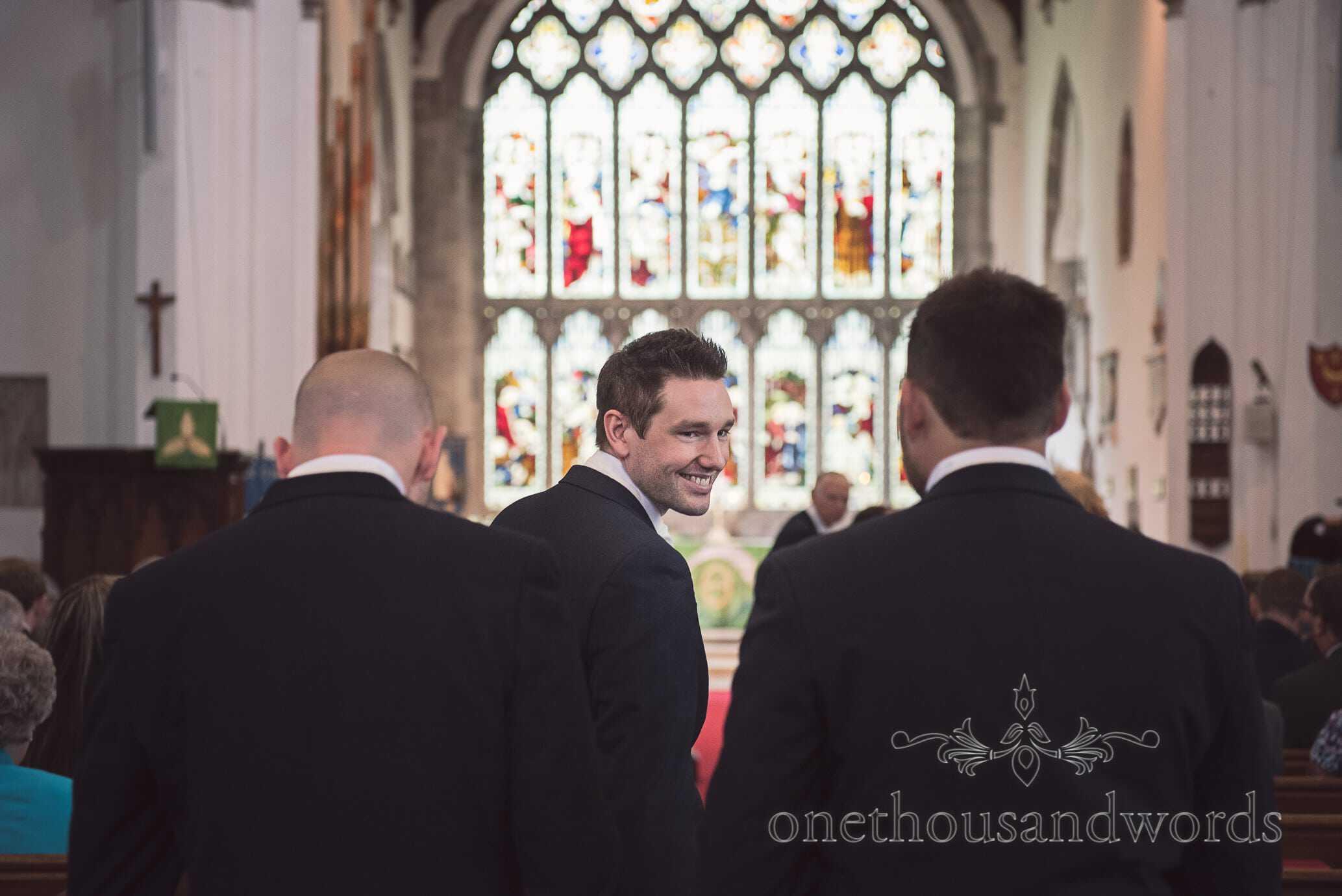 Groom smiles at best men as he enters Wareham church wedding