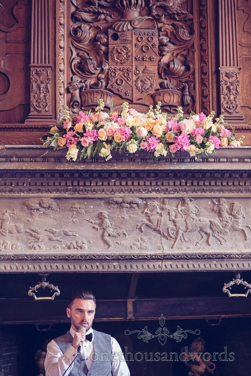 Grooms speech with wedding flowers and caved wooden coat of arms