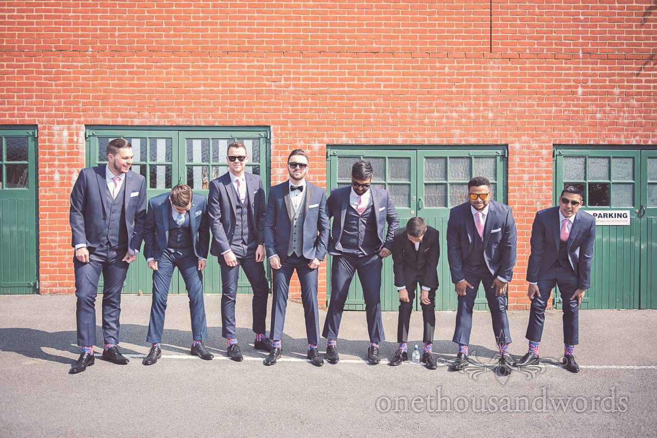 Groomsmen in blue suits show off their UK flag socks