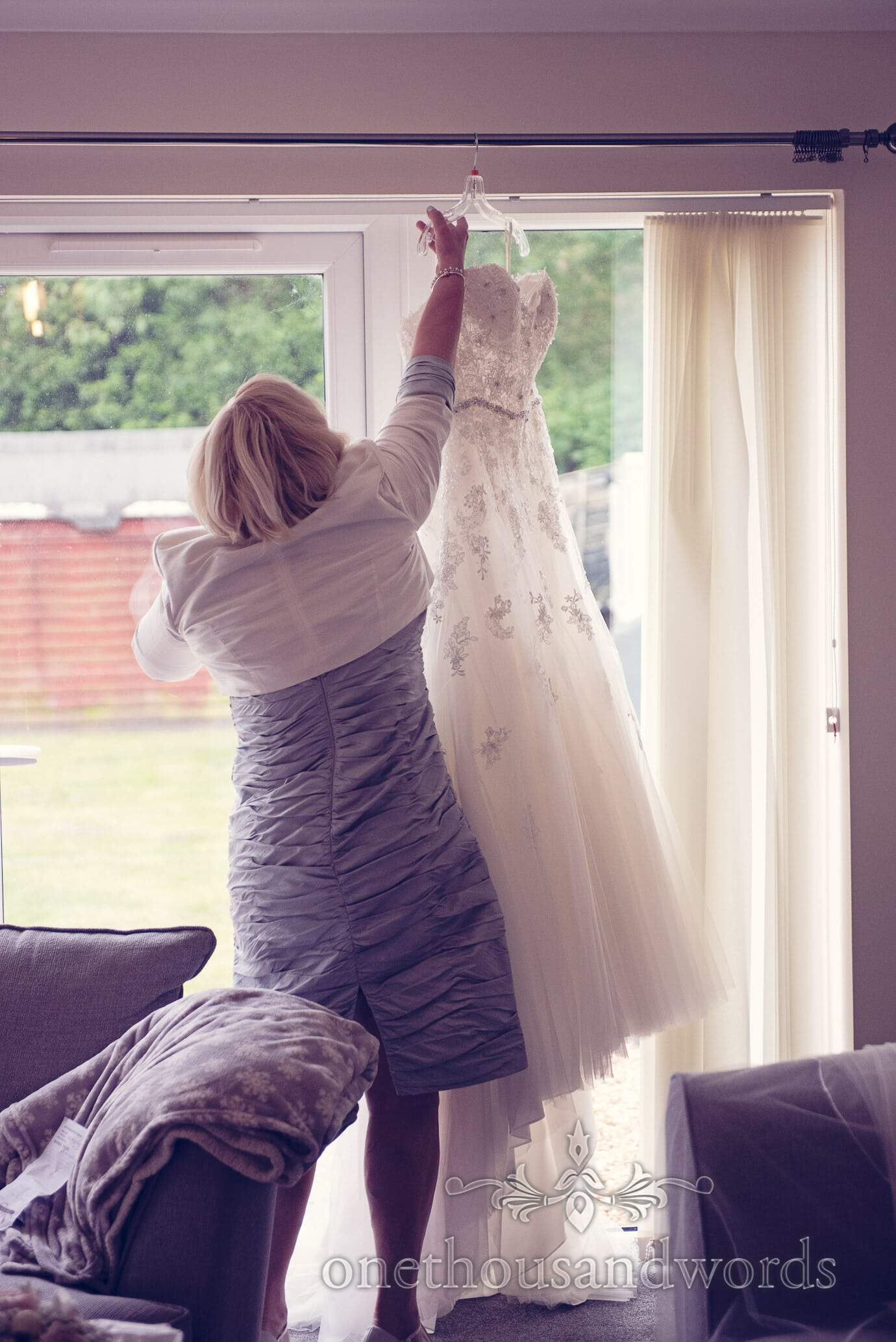 Mother of bride reaches for wedding dress in window