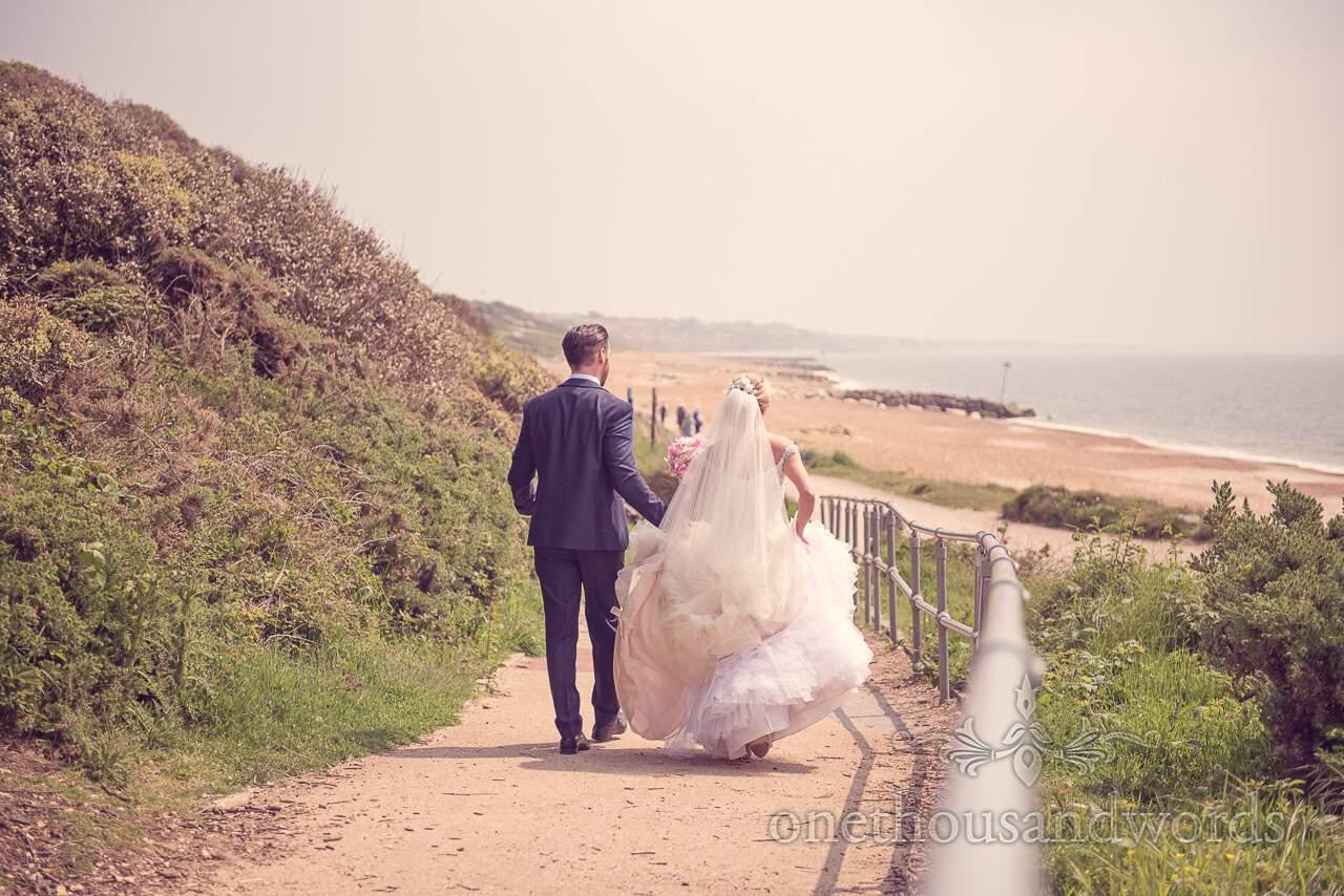 Newly wedding walk towards the beach at Rhinefield House Wedding