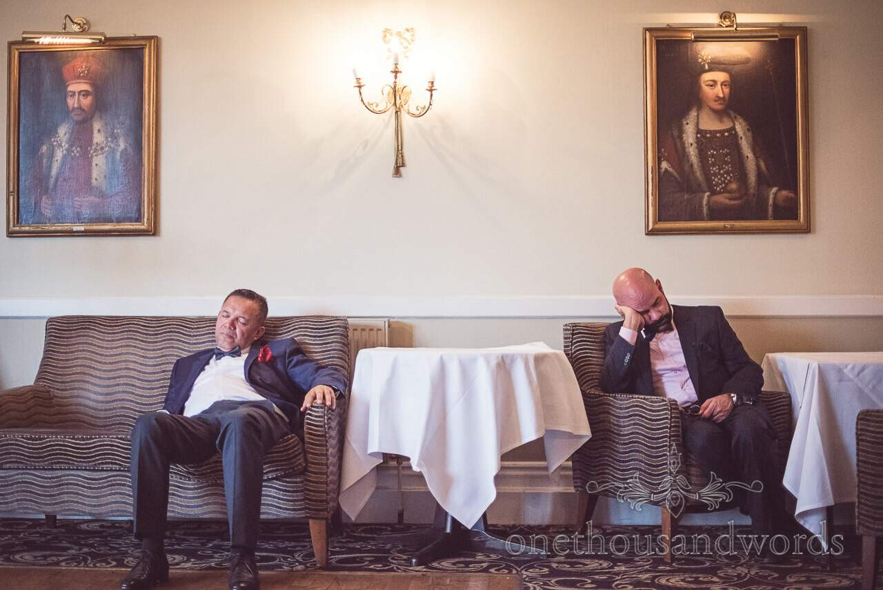 Tired wedding guests in bow ties sleep at Rhinefield House Wedding photographs