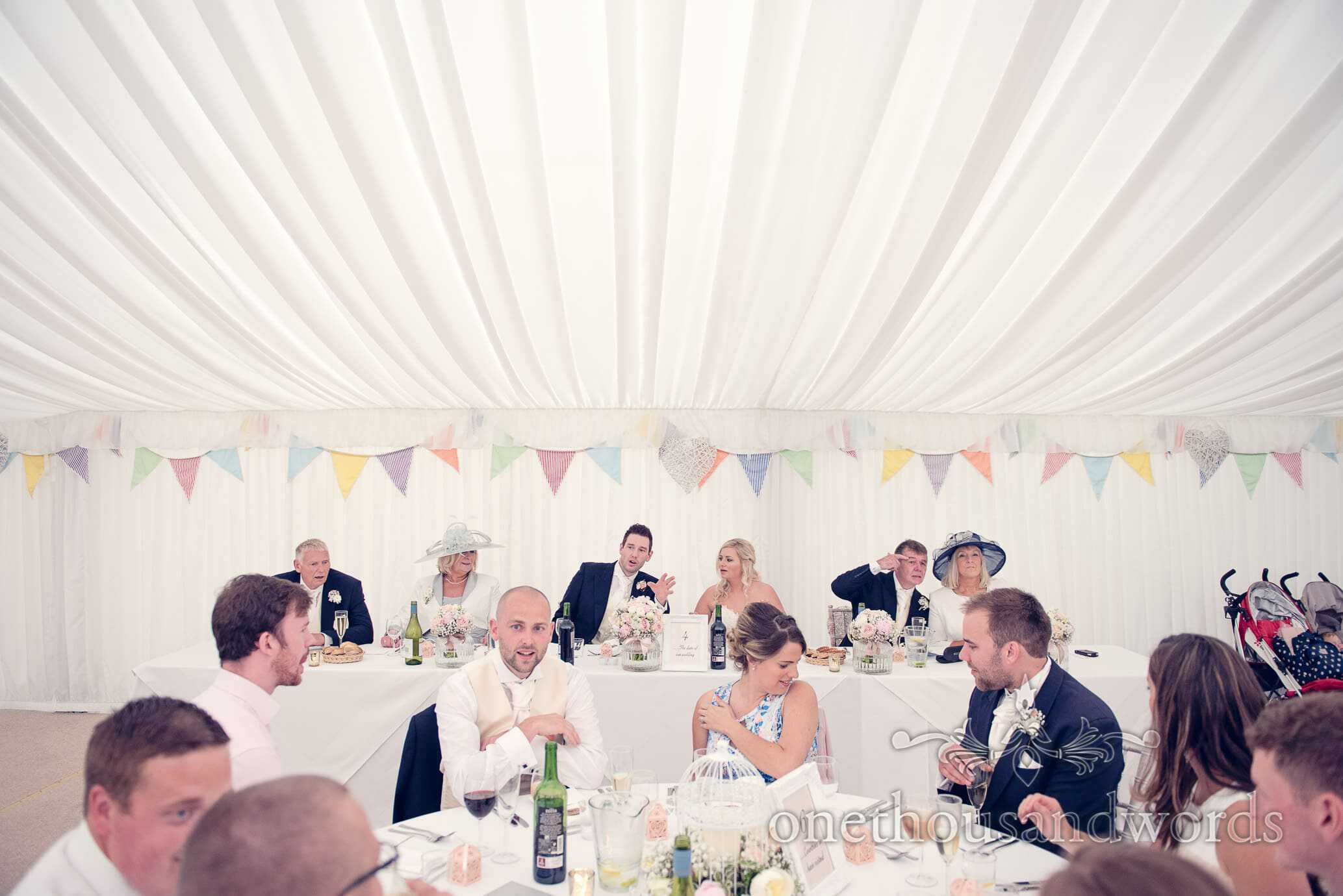 Top table with bunting in marquee at Deans Court Wedding venue