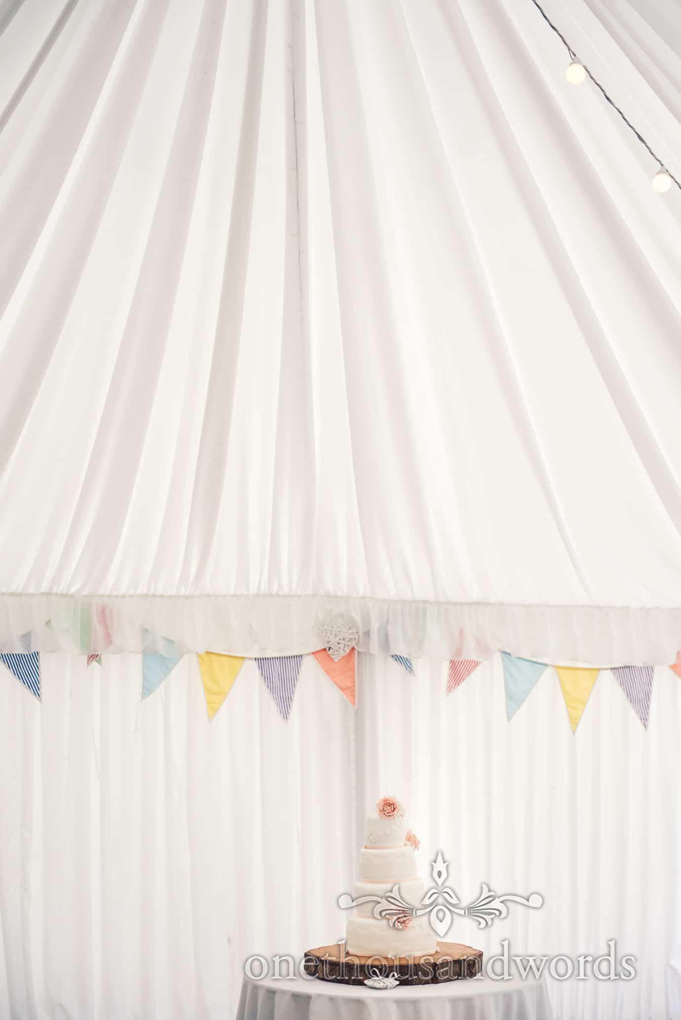 wedding cake on wood slice with bunting in marquee at Deans Court wedding