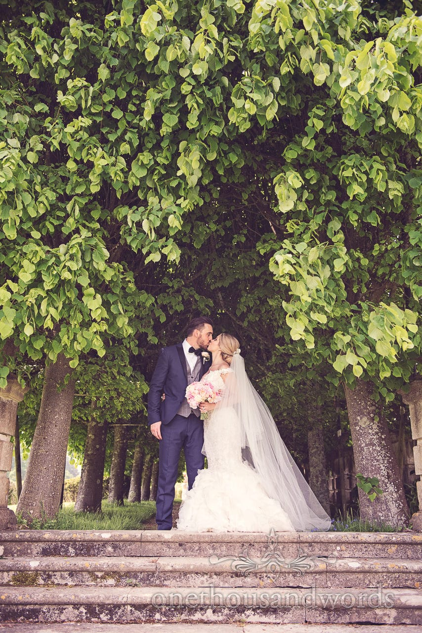 Wedding couple kiss in garden at Rhinefield House Wedding
