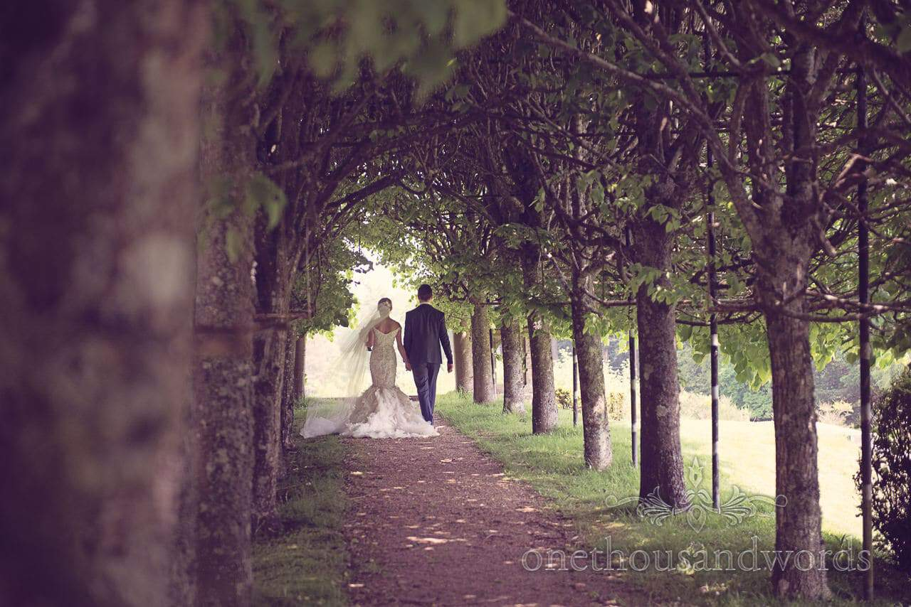 Wedding couple walk down tree tunnel at Rhinefield House Wedding