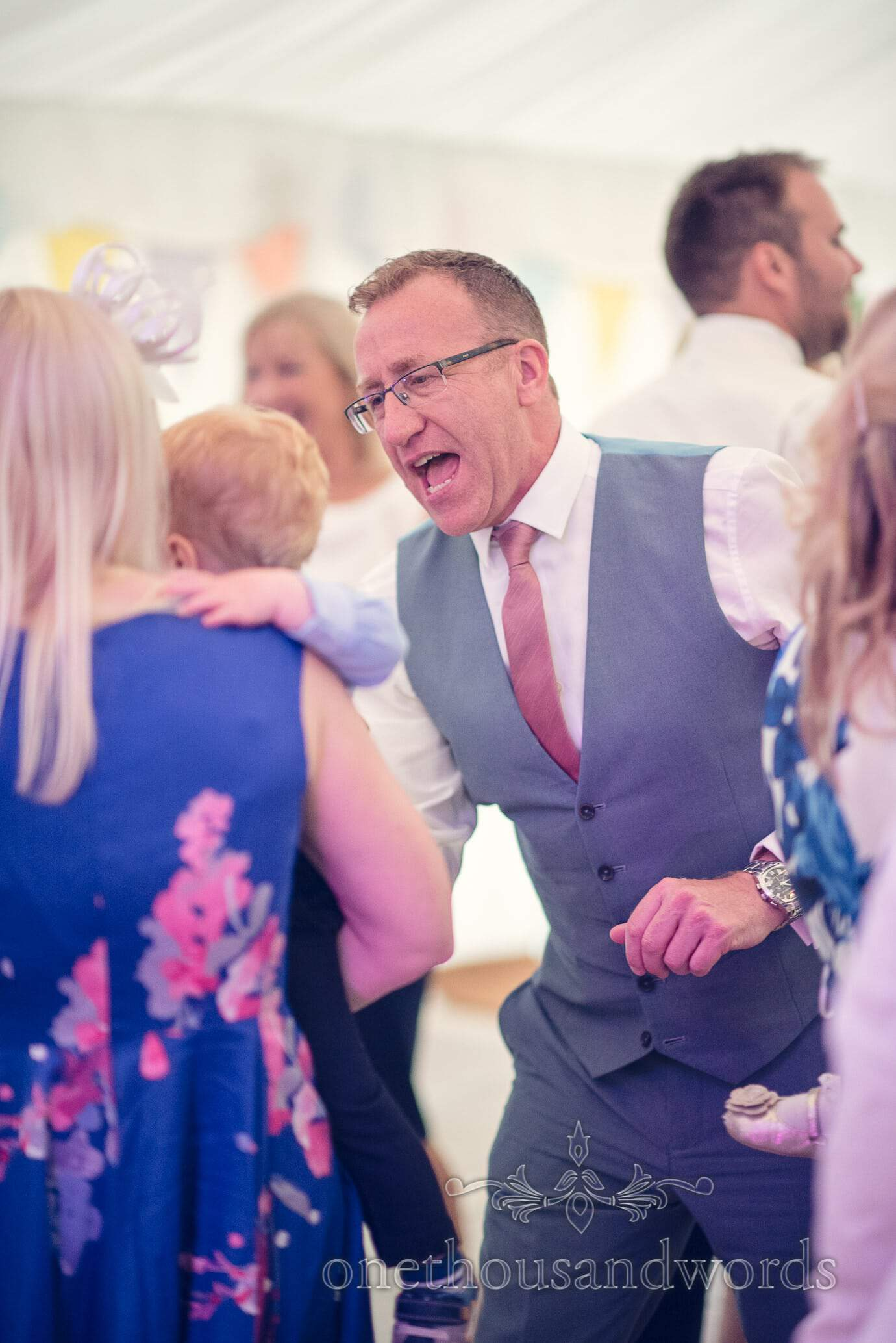 Wedding guest in blue waistcoat dances and sings at Deans Court Wedding