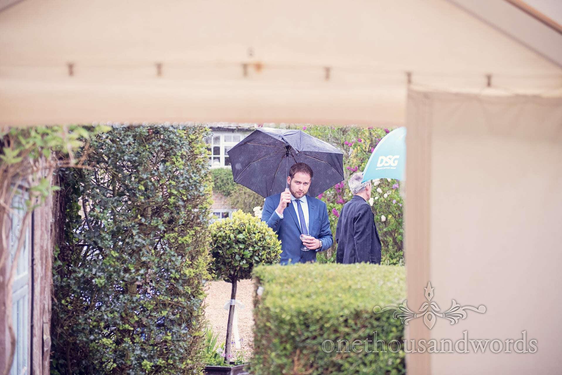 Wedding guest under umbrella at rainy wedding