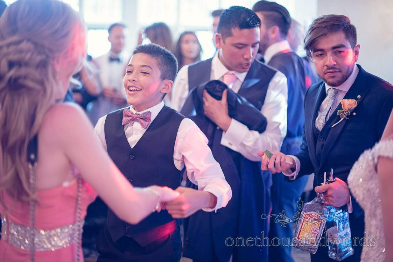 Wedding guest with bottles of tequila dances at Rhinefield House Wedding