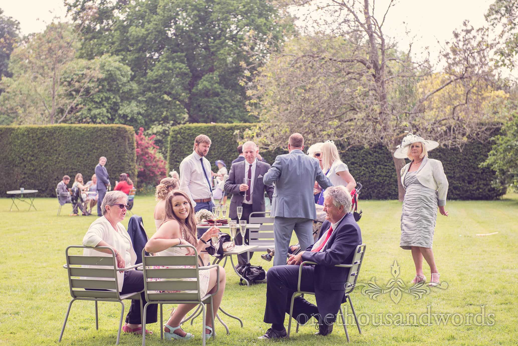 Wedding guests enjoy a drinks reception in the gardens at Deans Court wedding