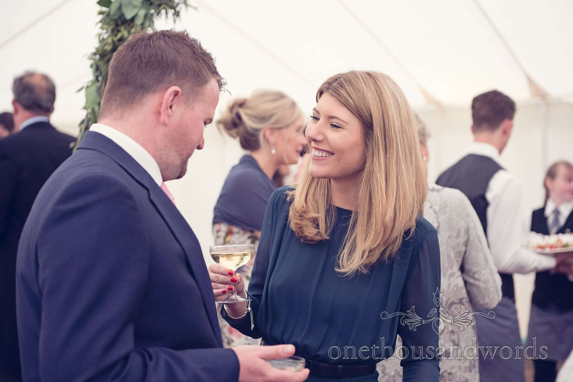 Wedding guests enjoy champagne drinks reception at marquee wedding