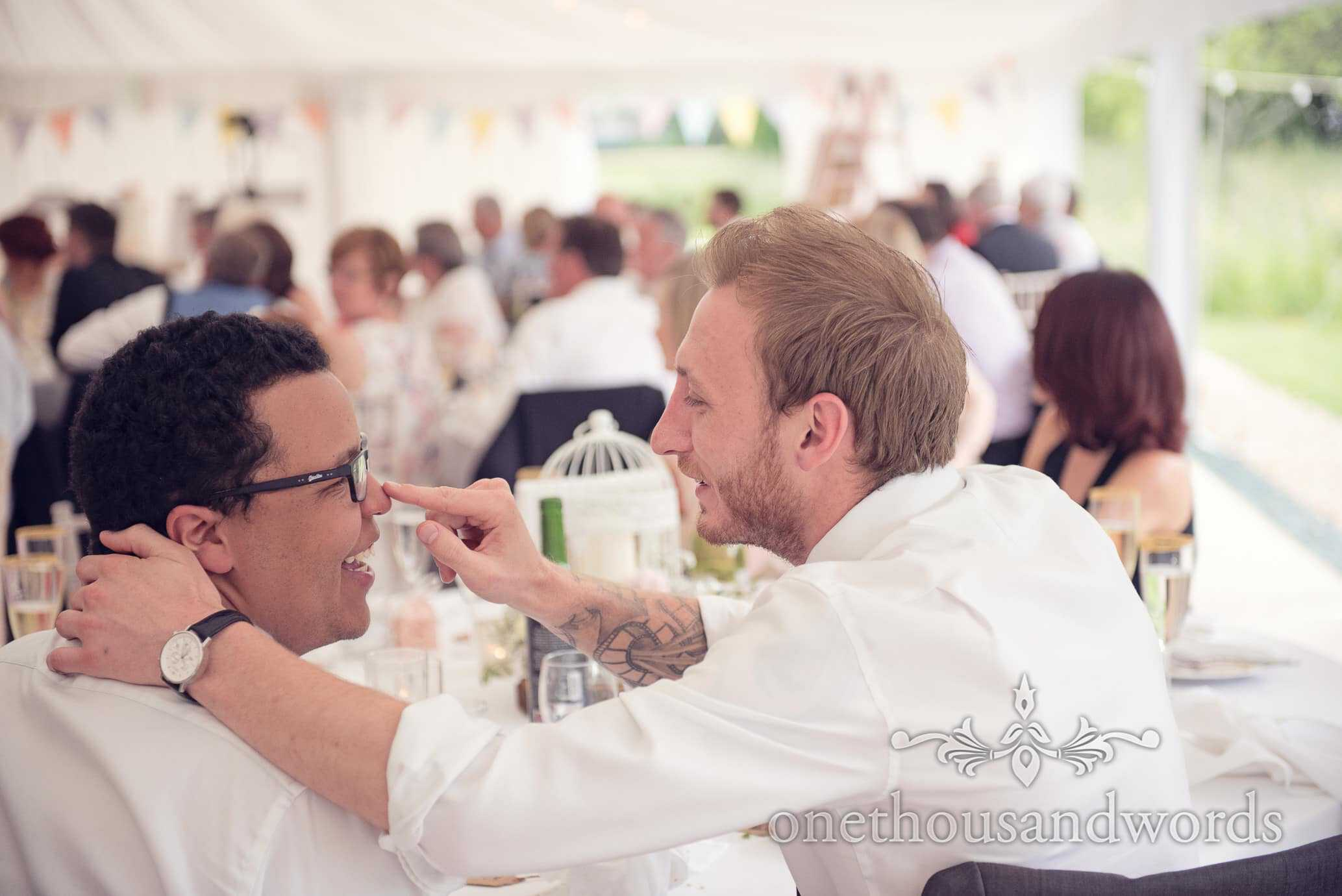 wedding guests joking in marquee at Deans Court Wedding