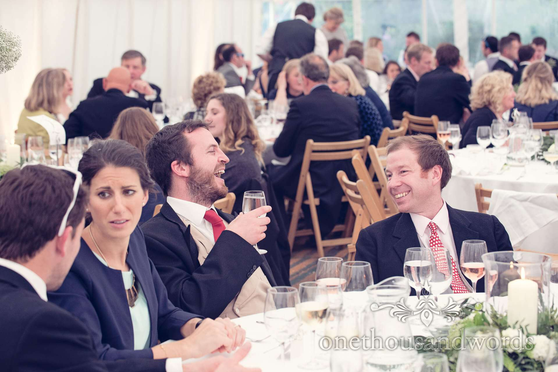 Wedding guests laugh at Marquee wedding in Wareham, Dorset
