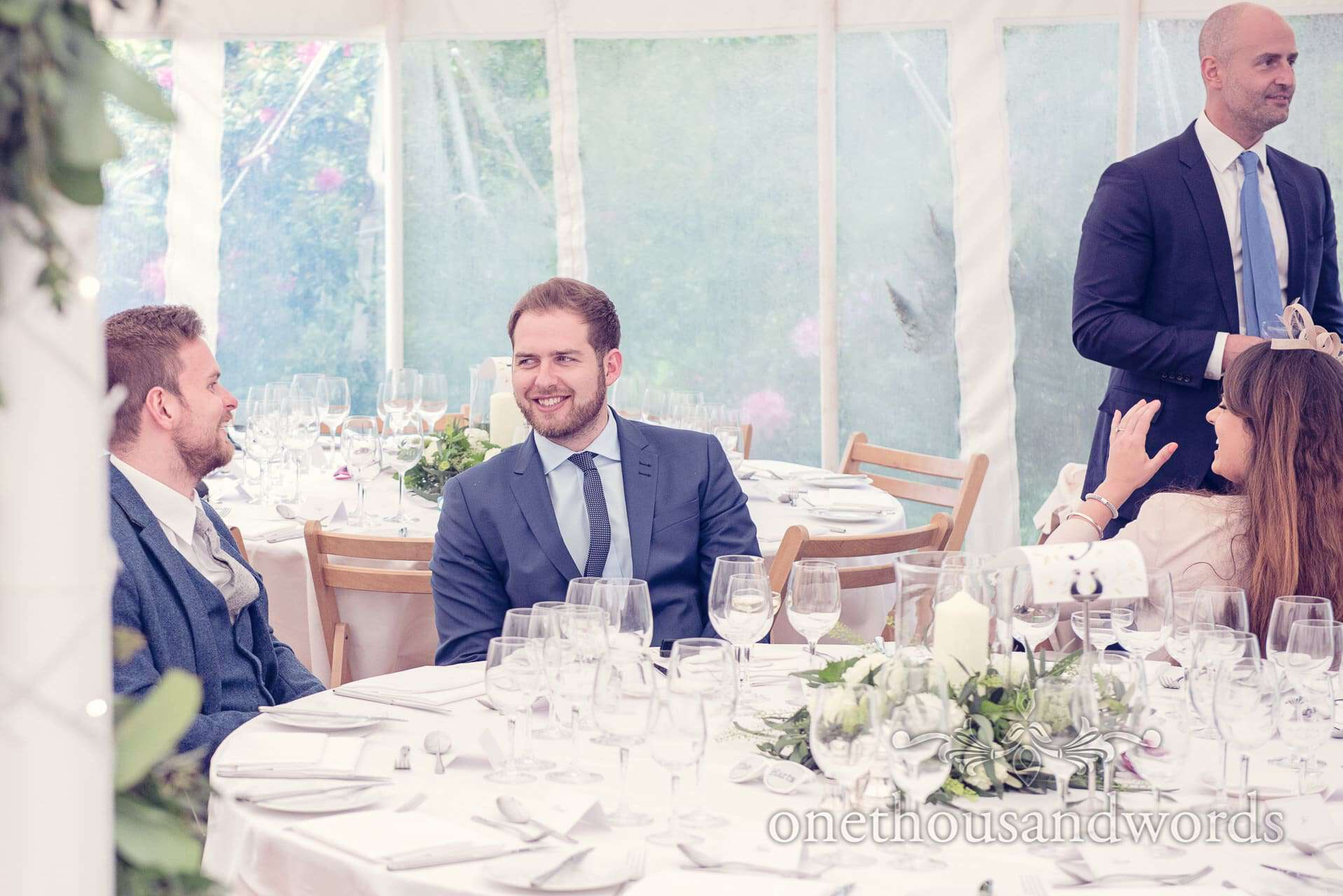 Wedding guests sit at tables in wedding marquee