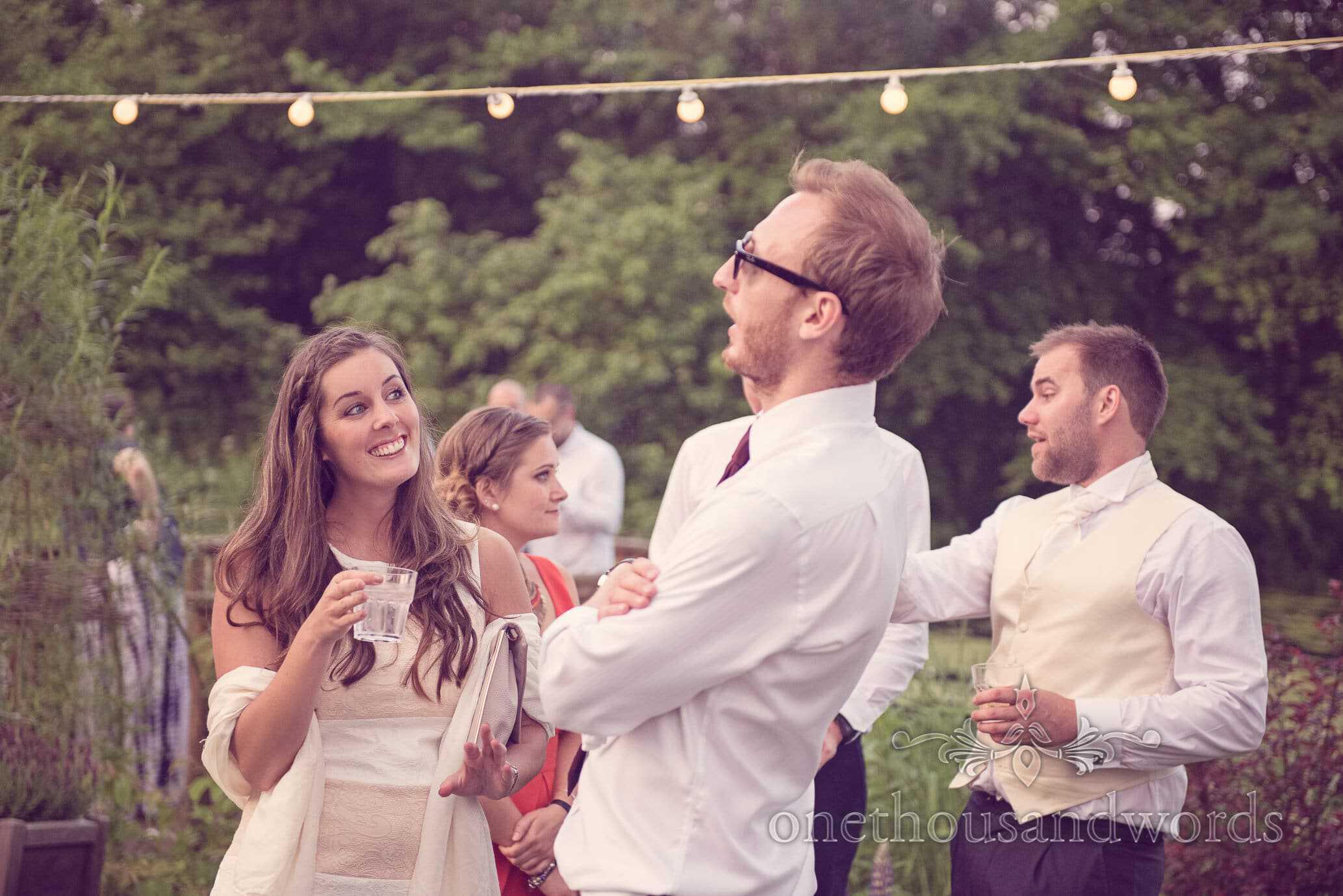 Wedding guests under festoon lighting in garden at Deans Court Wedding