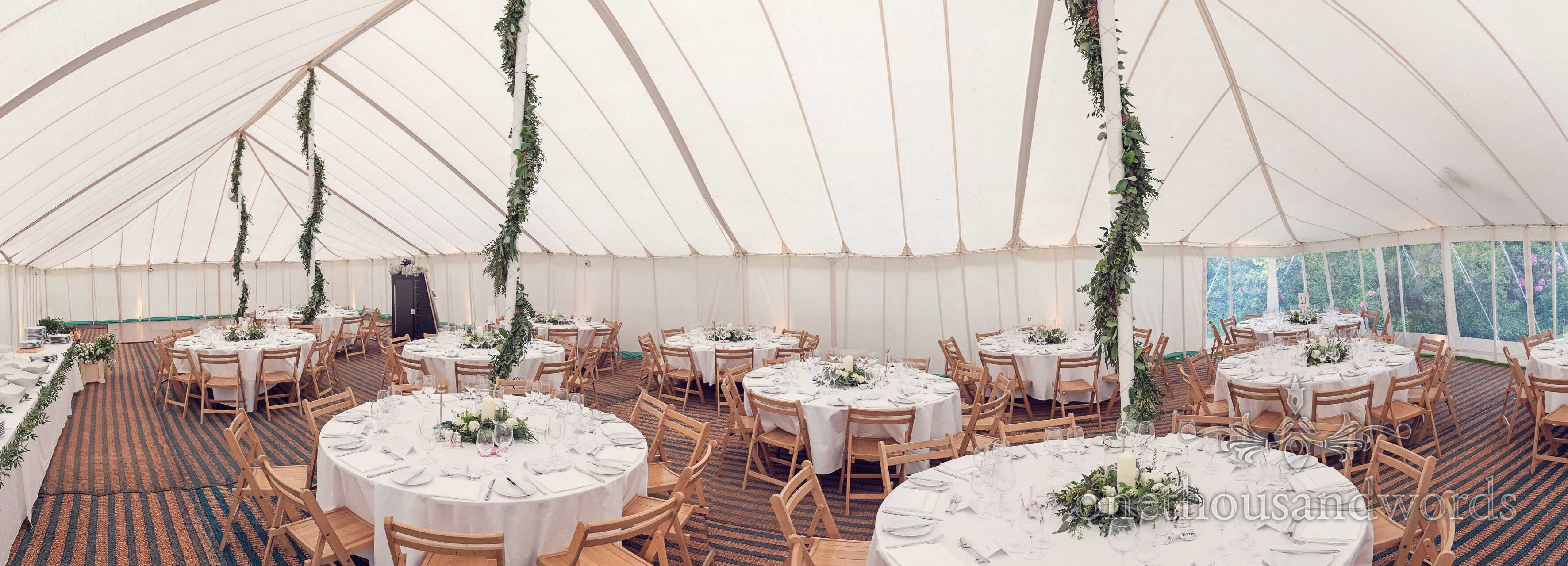 Wedding marquee table layout with white wedding flowers