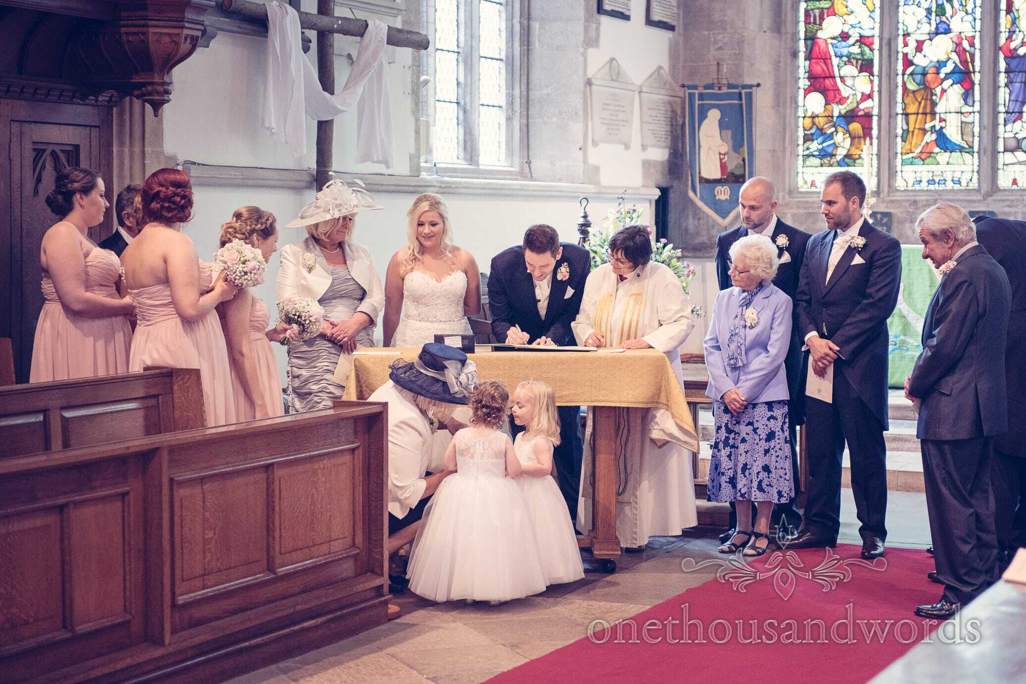 Wedding party with bride and groom signing the register at church wedding