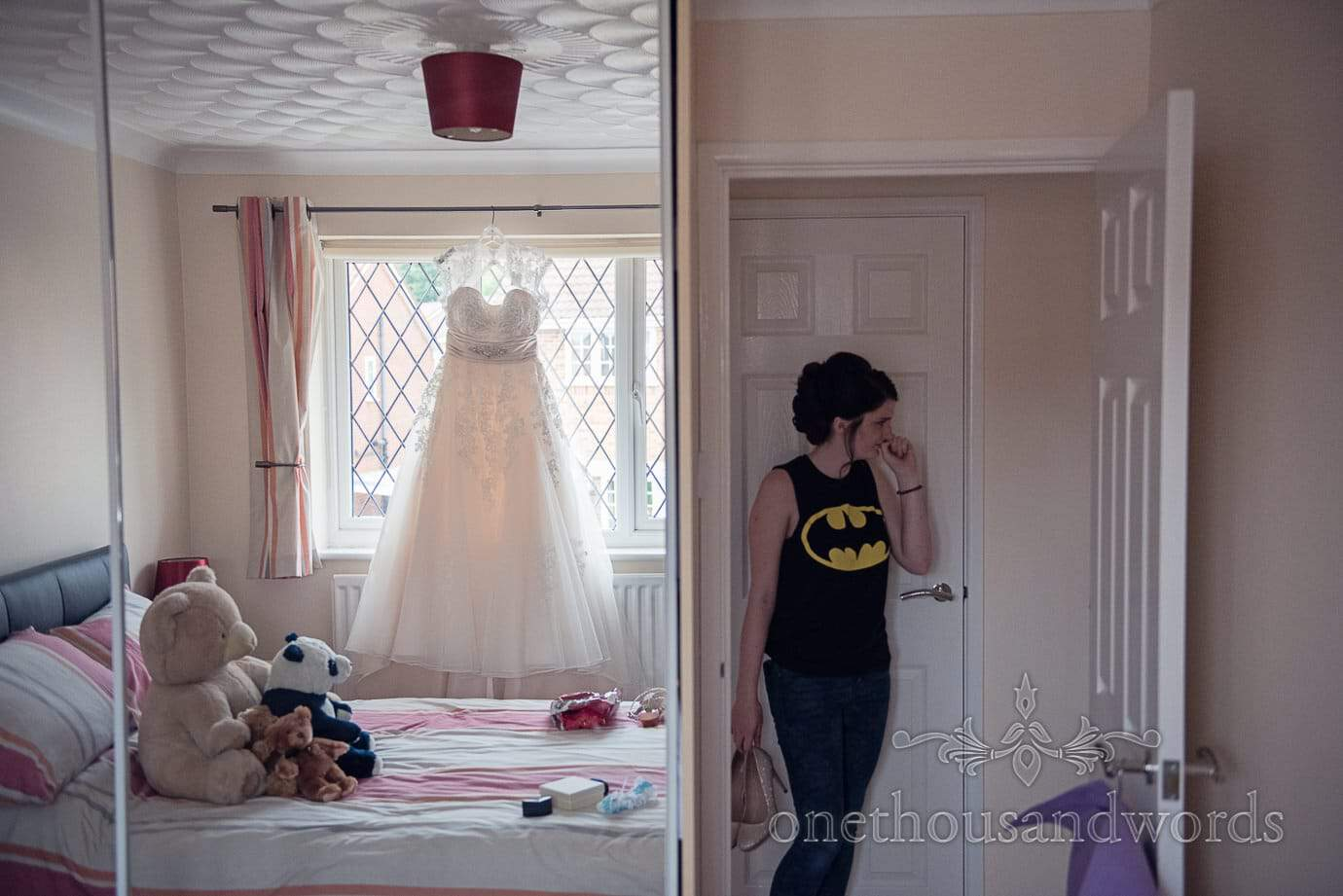 White wedding dress hangs in bedroom window on wedding morning