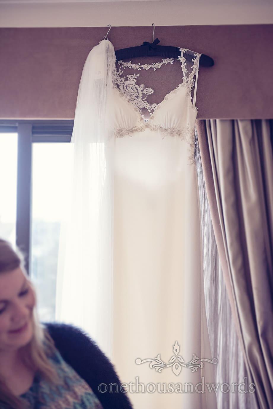White wedding dress hangs in window before Italian Villa Wedding Photographs