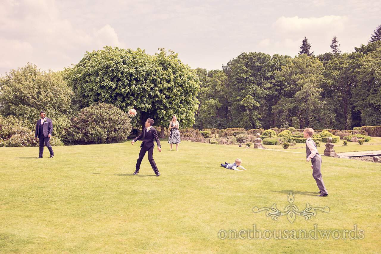 Younger guests play football on lawn at Rhinefield House Wedding