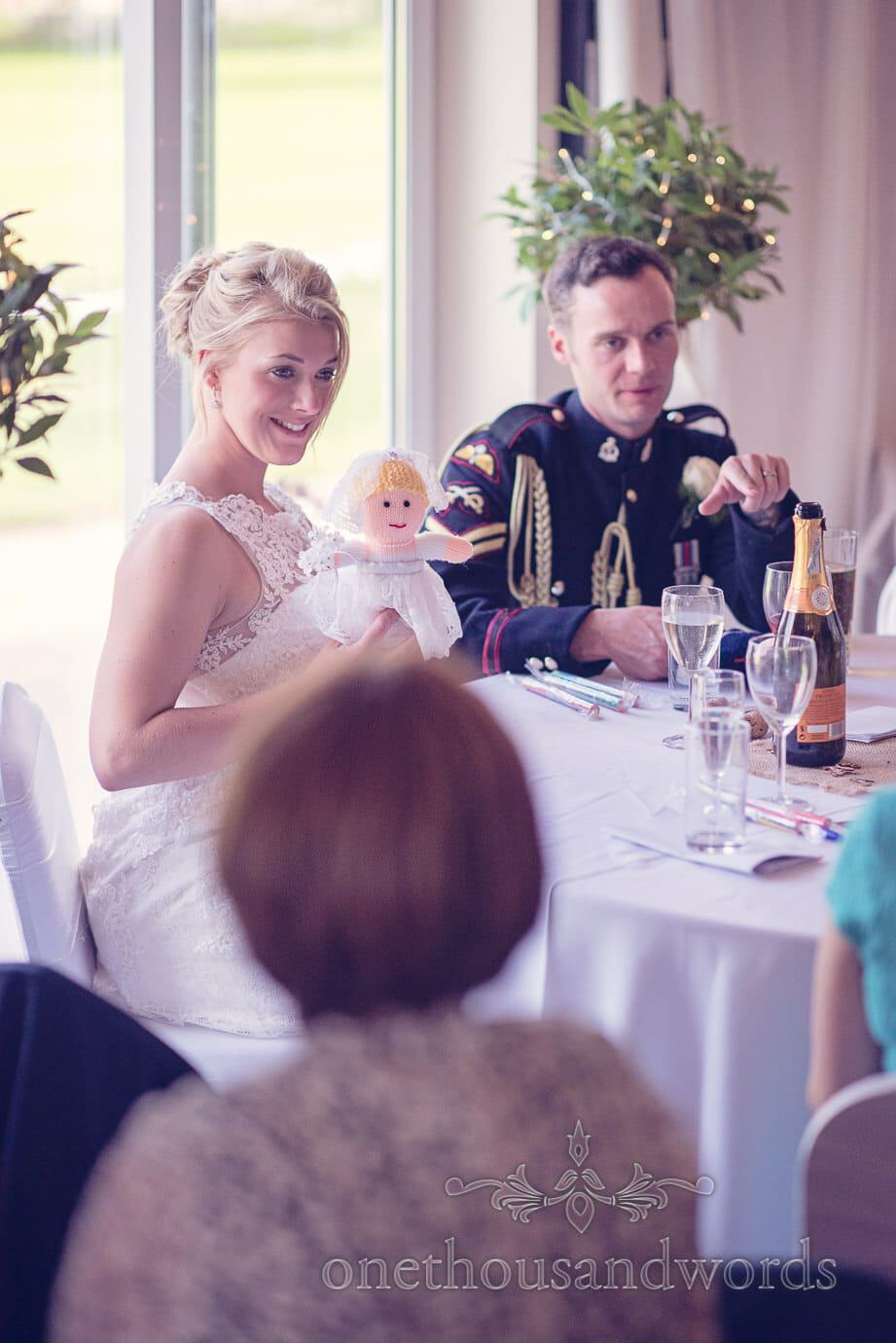 Beautiful blonde Bride shows off knitted bride doll version of herself