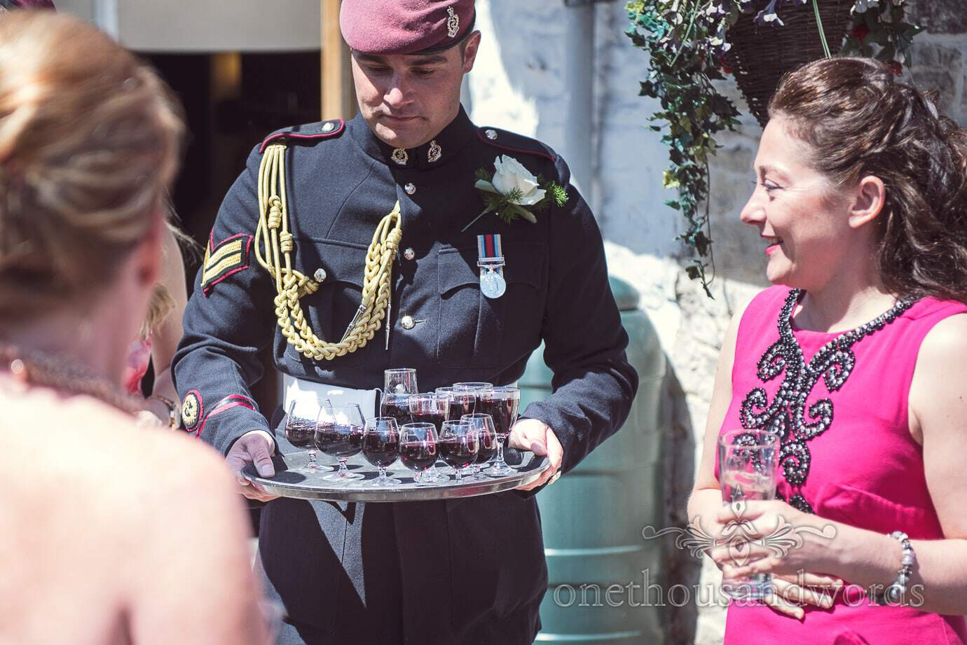 Best man in military uniform carries a tray of port on wedding morning