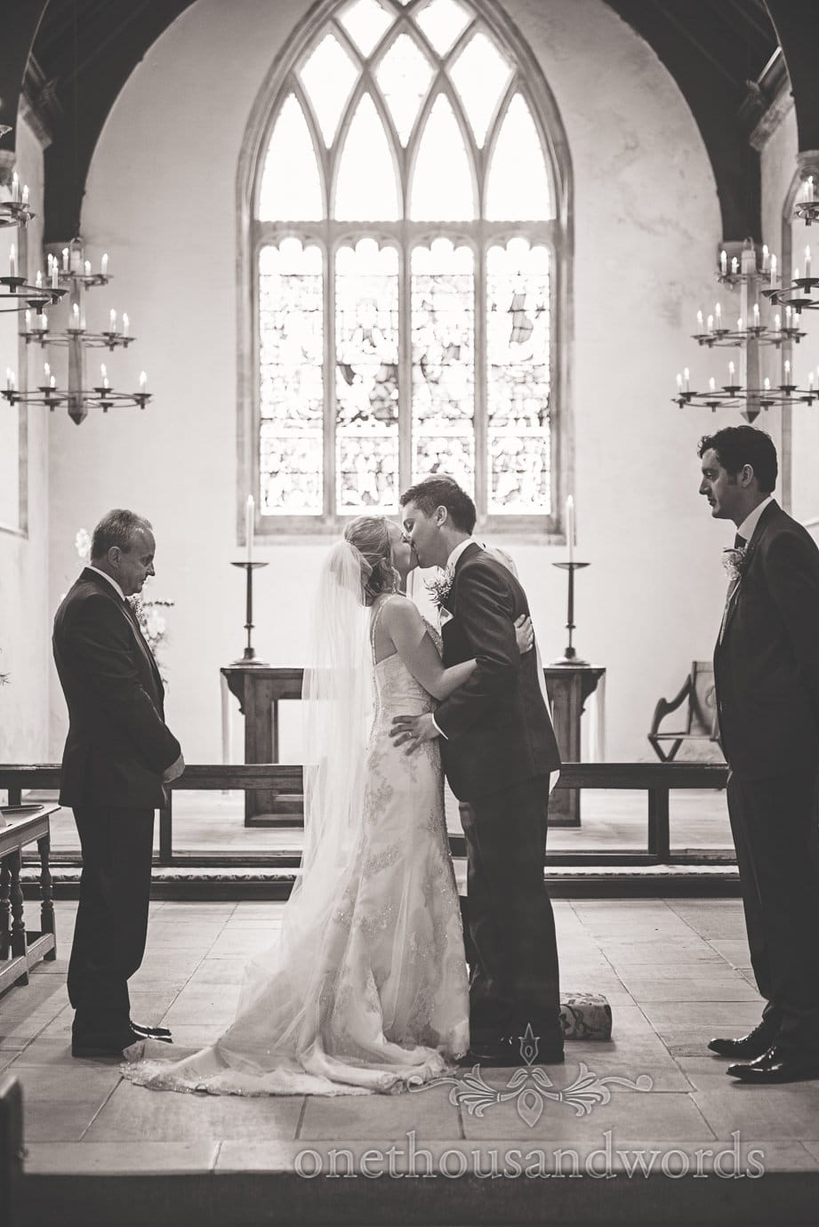 Black and white wedding photograph of first kiss at church wedding