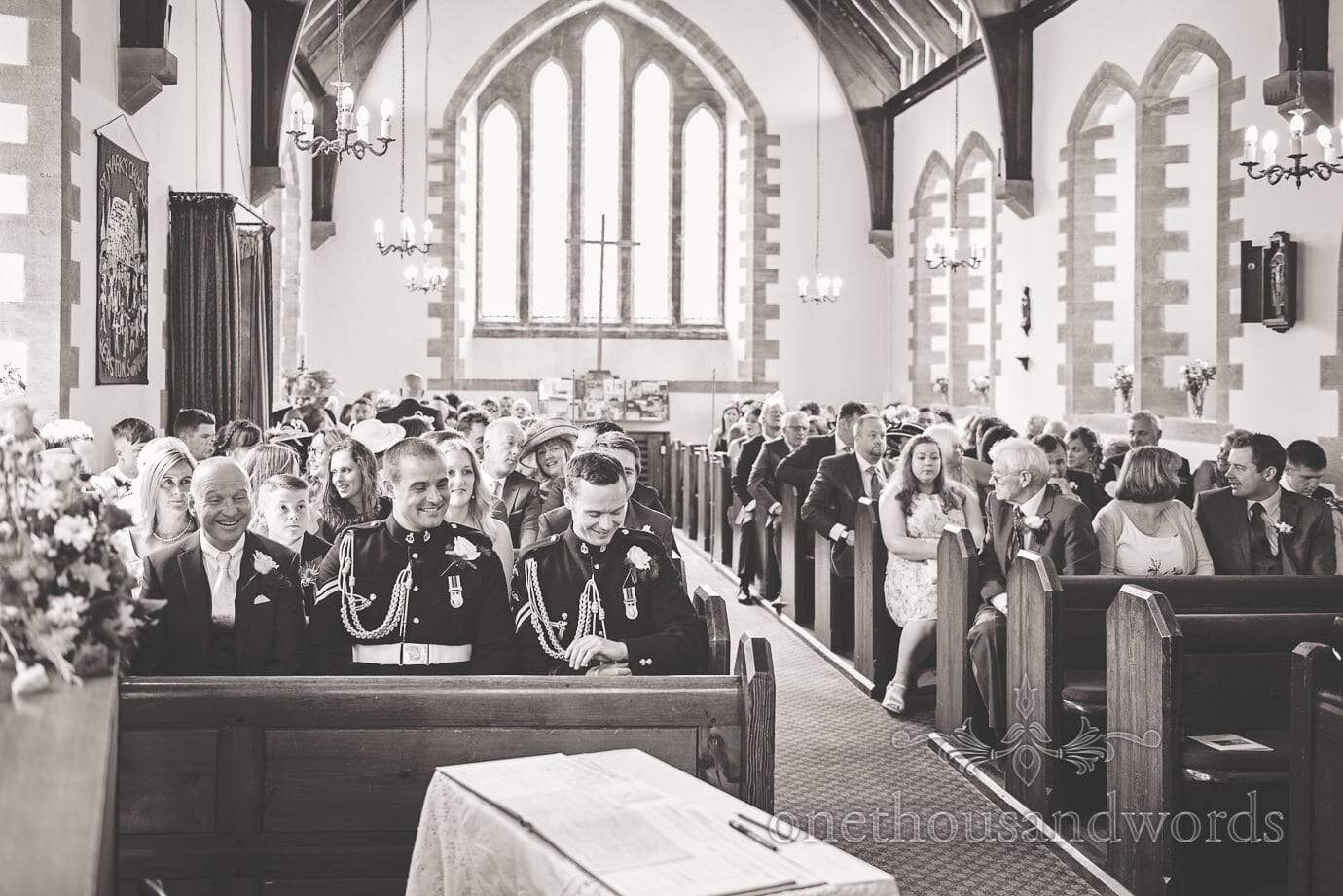 Black and white wedding photograph of groom waiting for bride in church