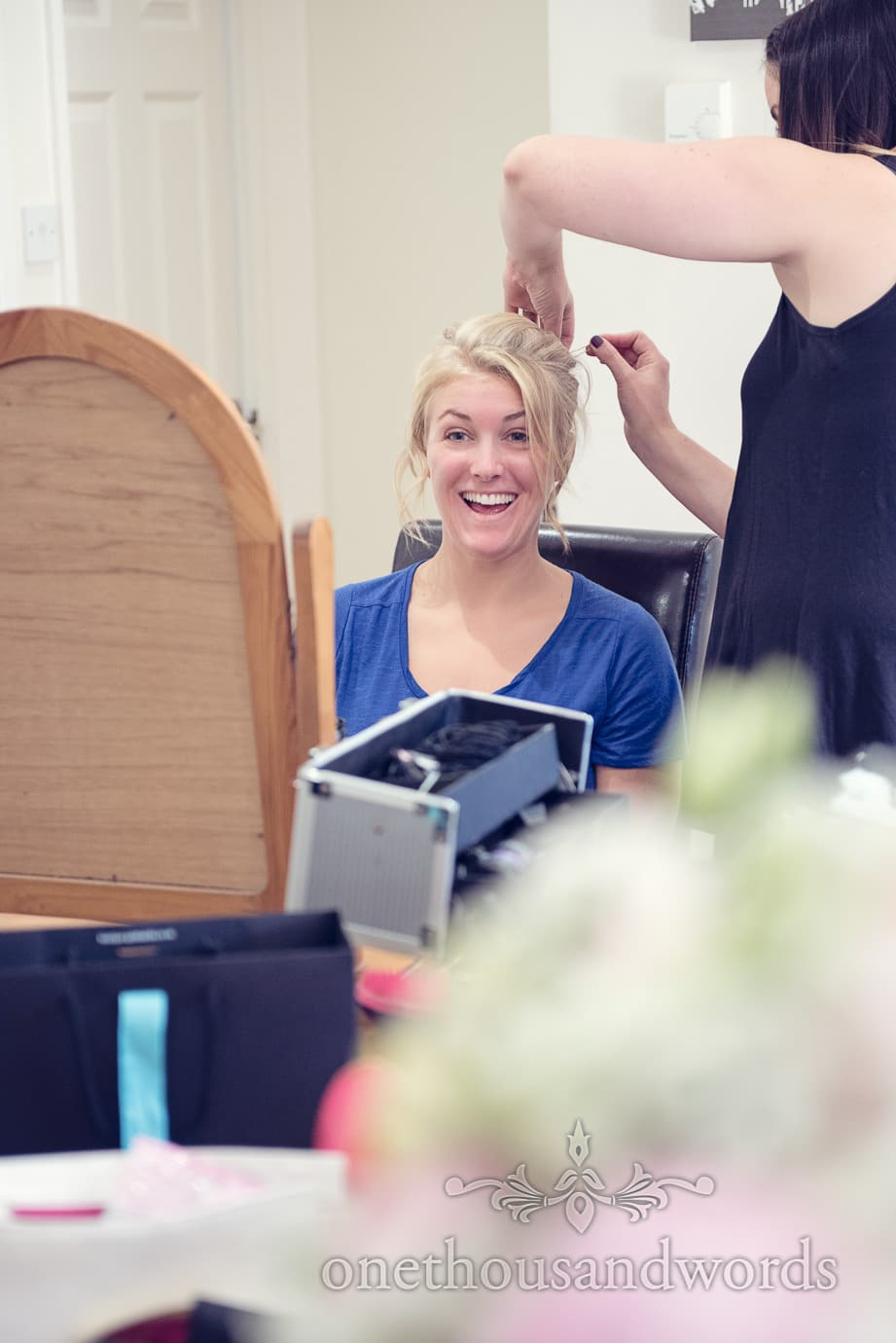 Blonde bride has wedding hair styled at home on wedding morning