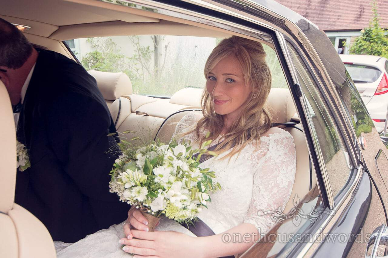 Blonde bride with white and green wedding flowers in Bentley wedding car