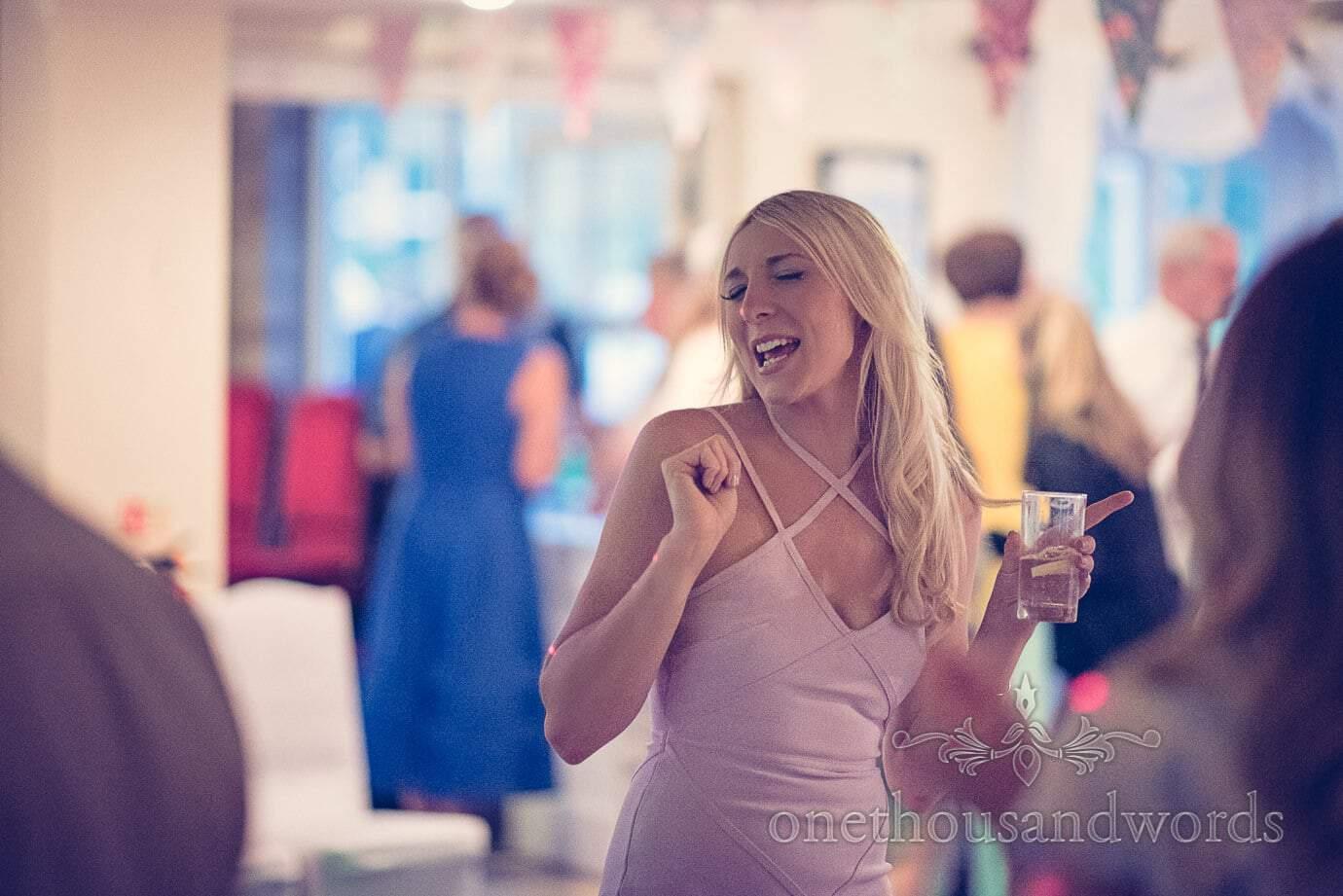 Blonde wedding guest in pink dress dances to wedding disco