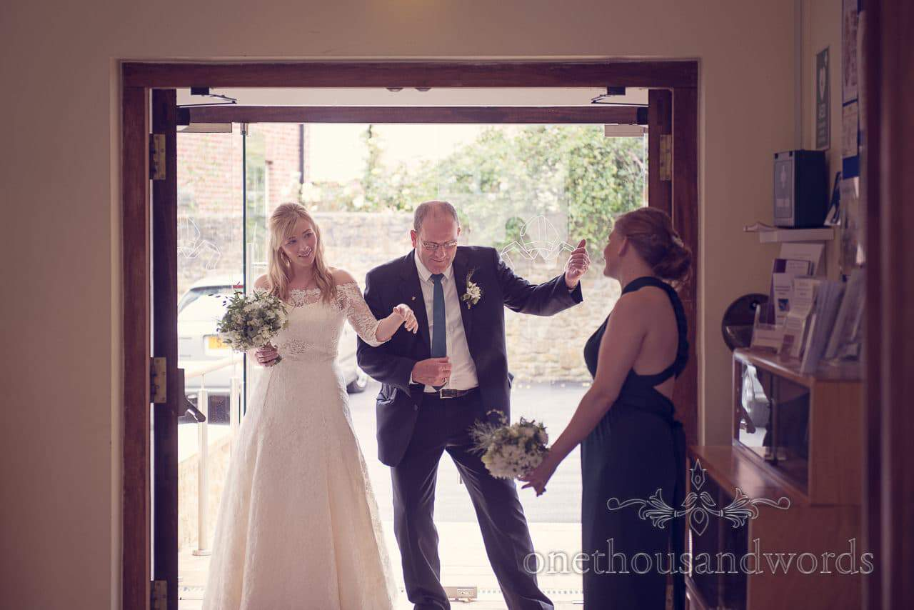 Bride and father of bride dance anf play air instruments in church doorway